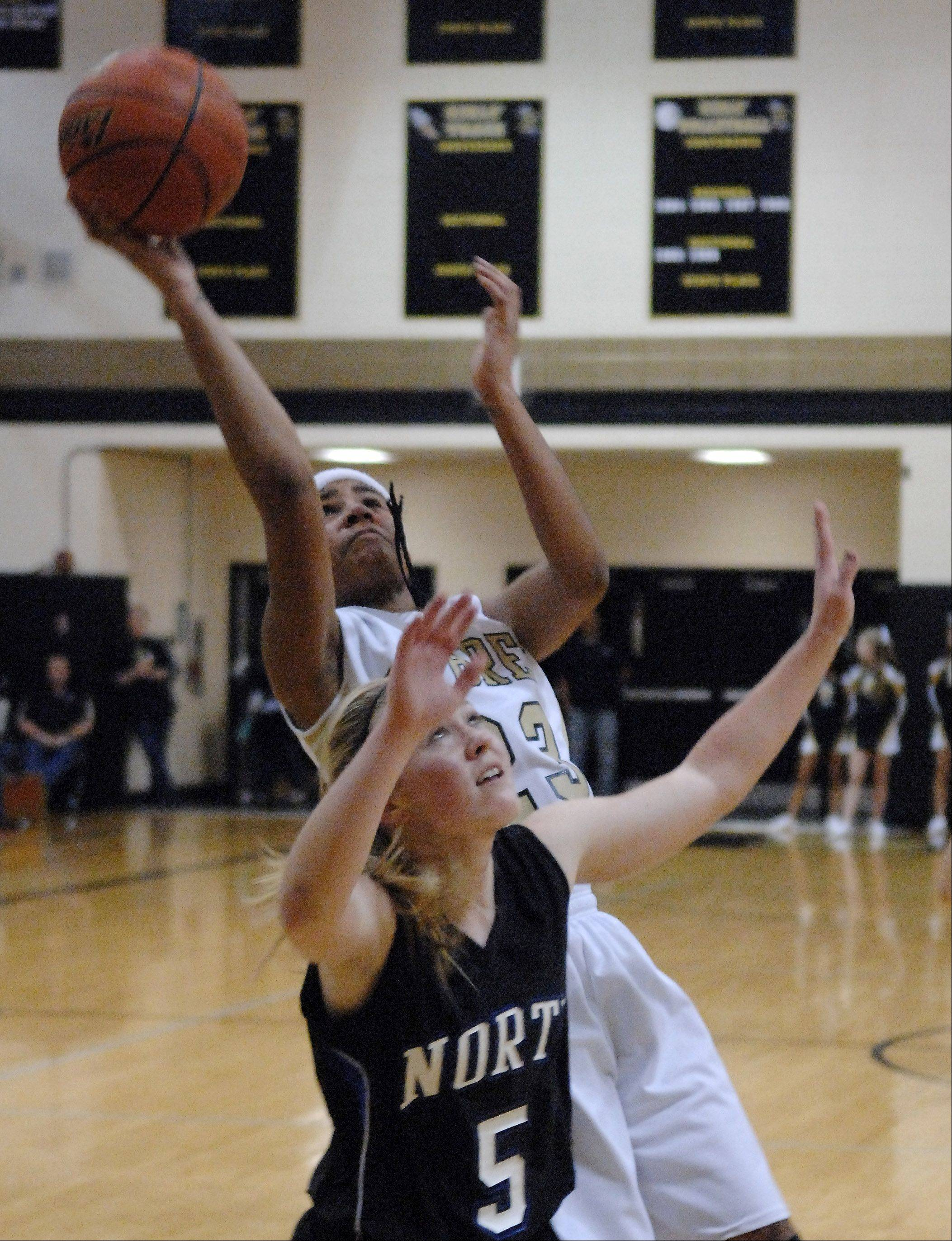 Streamwood's Deja Moore puts up a shot over St. Charles North's Natalie Winkates after grabbing an offensive rebound during Friday's game at Streamwood.