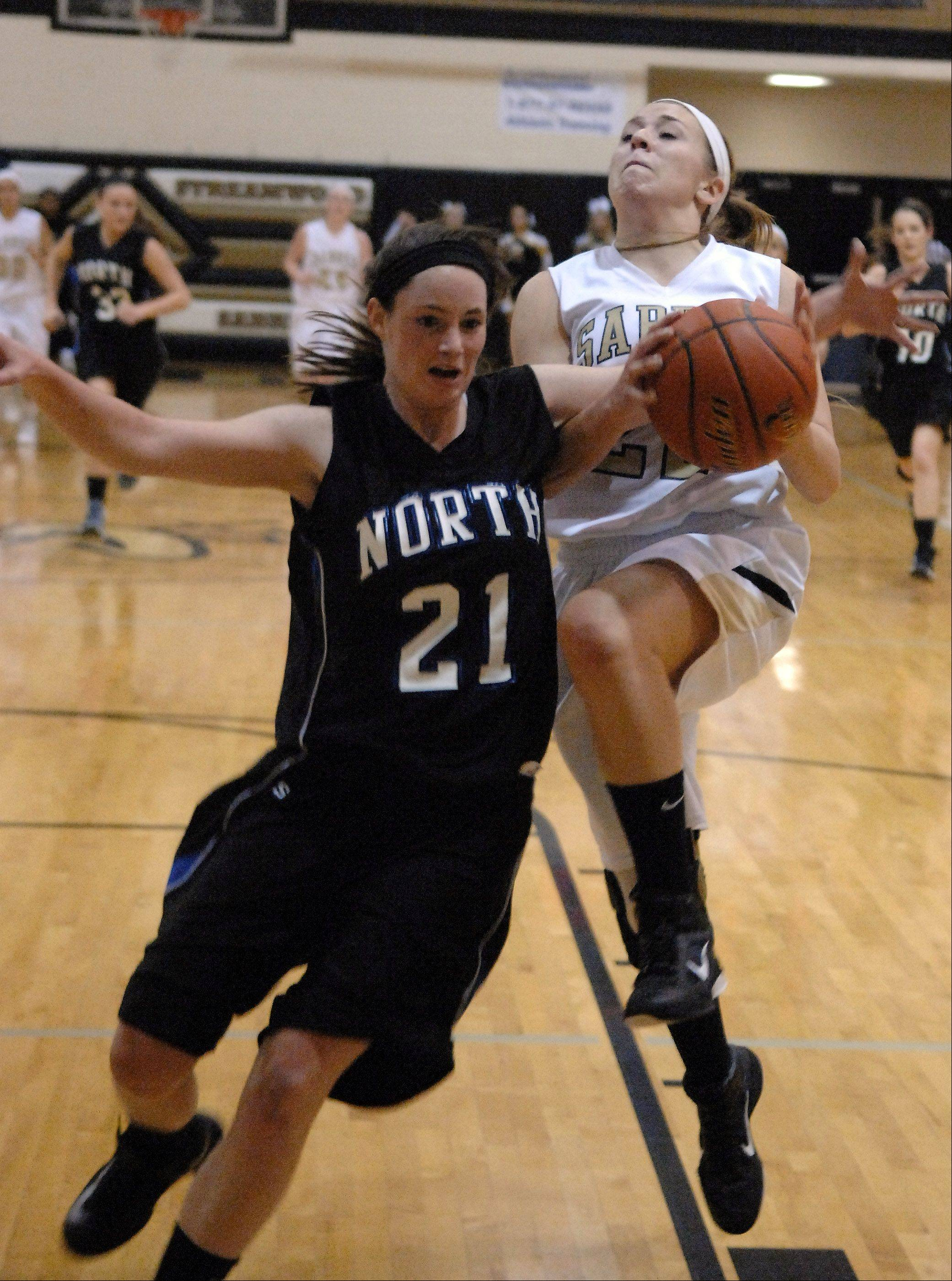 Streamwood's Holly Foret gets fouled by St. Charles North's Alex Silverman while driving to the basket during Friday's game at Streamwood.