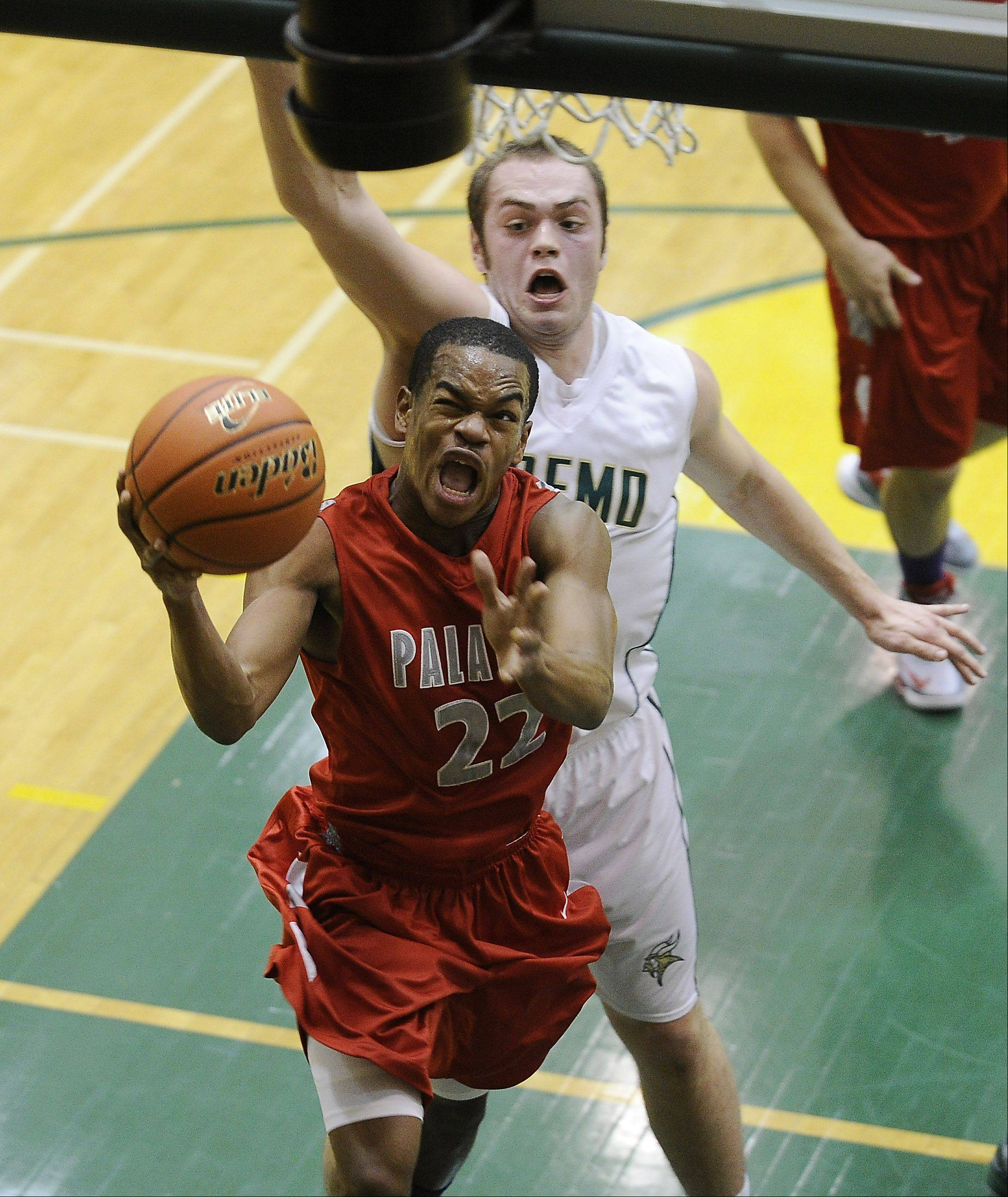 Palatine's Jordan Jarrett drives for the basket under pressure against Fremd.