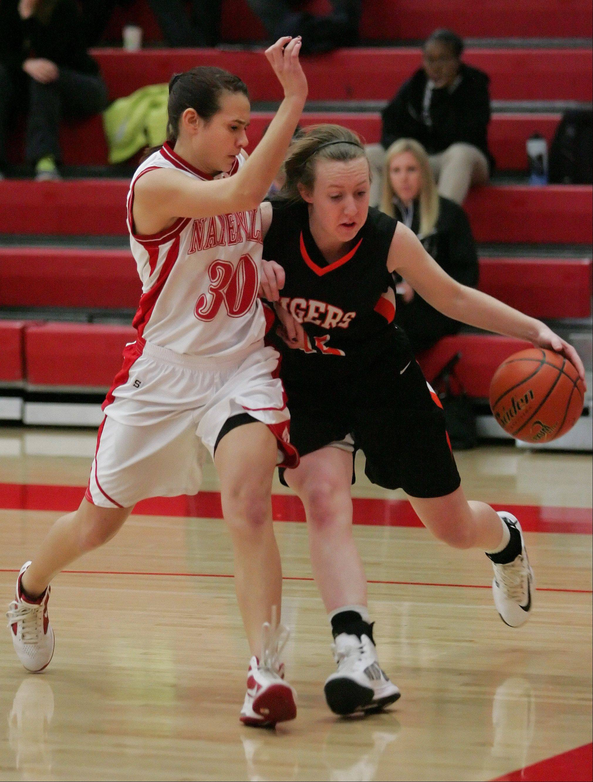 Meghan Waldron of Wheaton Warrenville South, right, drives the ball around Shannon Ryan of Naperville Central in girls basketball action on Tuesday in Naperville.