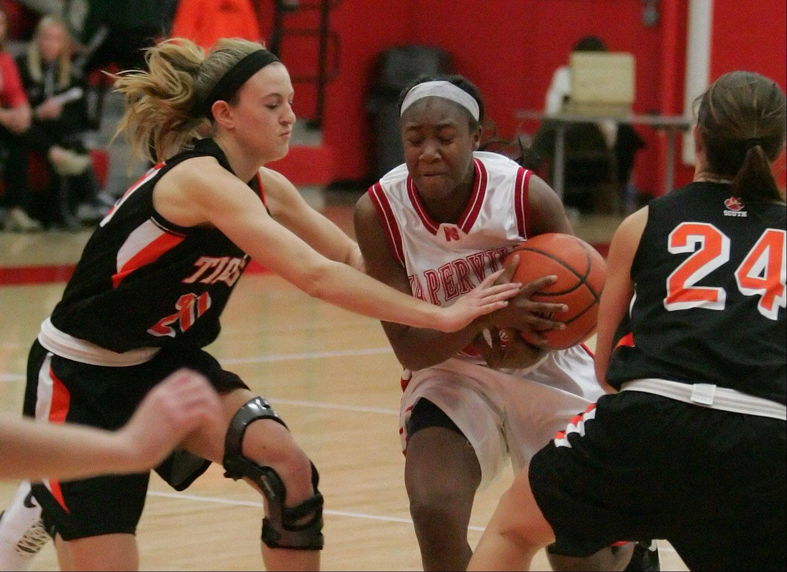 Cierra Stanciel of Naperville Central, right, tries to keep possession of the ball as Kelly Langlas of Wheaton Warrenville South defends in girls basketball action on Tuesday in Naperville.