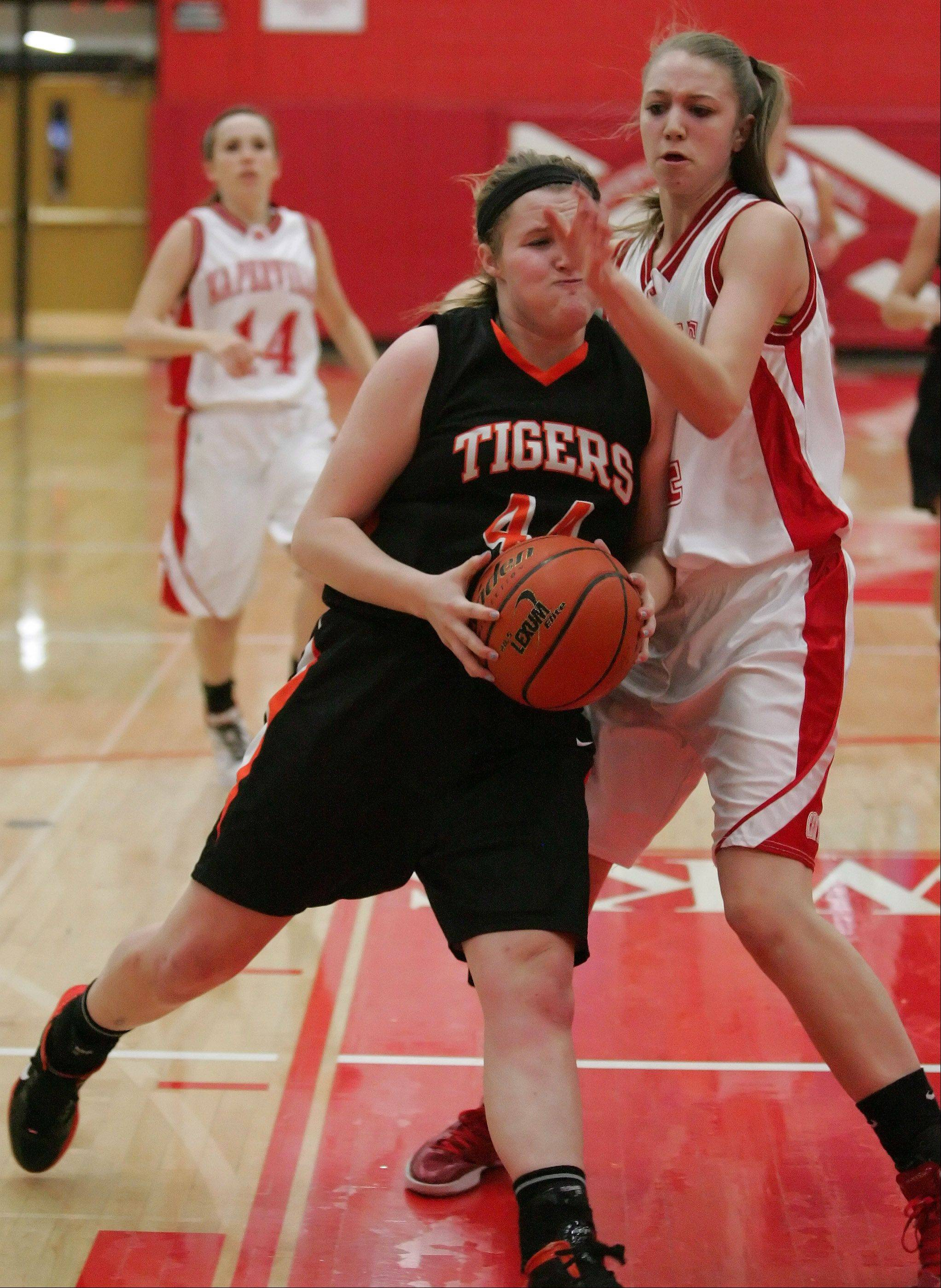 Olivia Linebarger, left, of Wheaton Warrenville South collides with Jamie Cuny of Naperville Central as she moves towards the basket in girls basketball action on Tuesday in Naperville.