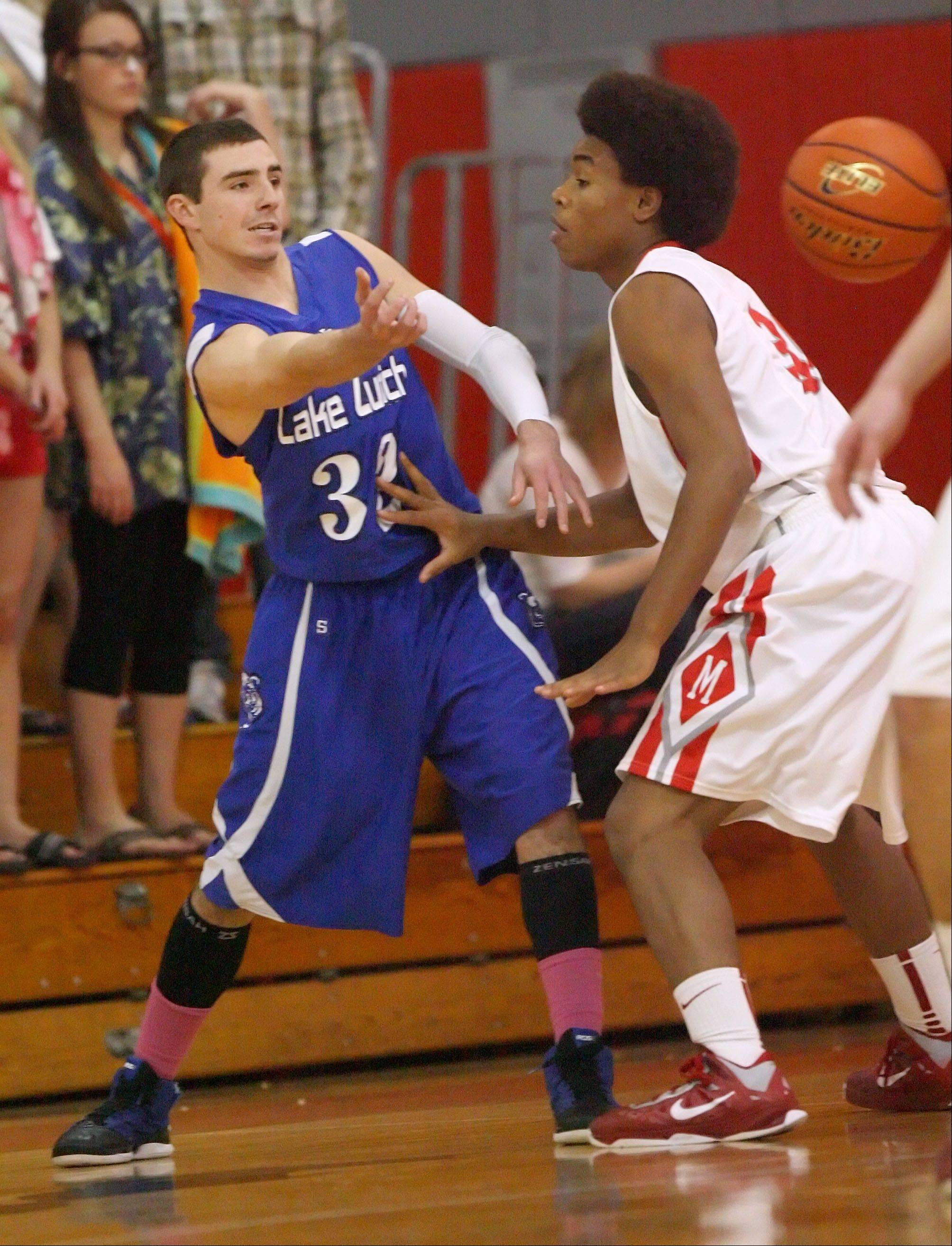 Lake Zurich's John Repplinger, left, dishes off the ball around Mundelein's Cliff Dunigan on Tuesday night at Mundelein.