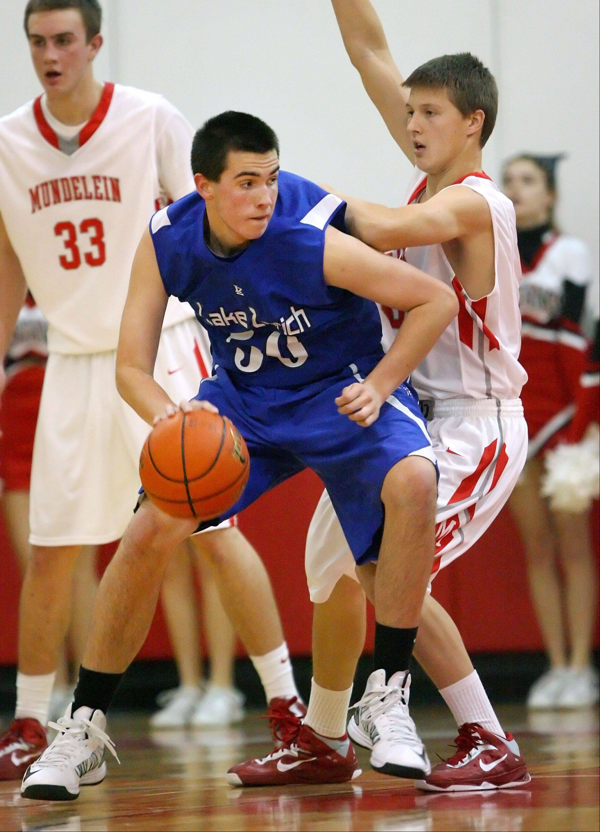 Lake Zurich's Will McLaughry, left, backs in on Mundelein's TJ Michalski.