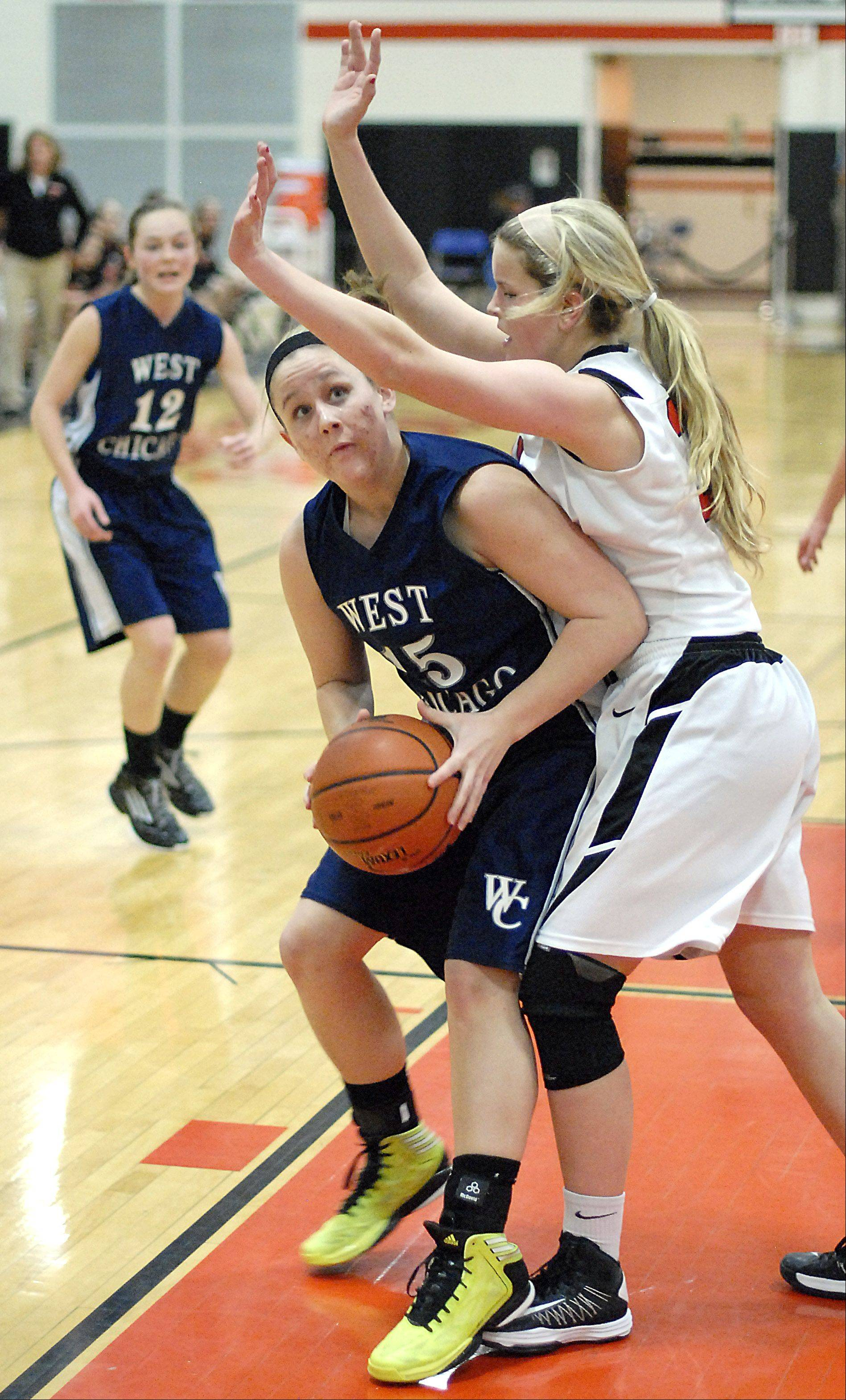 West Chicago's Kylee Gunderson looks to the hoop for a shot against the defense of St. Charles East's Hannah Nowling .