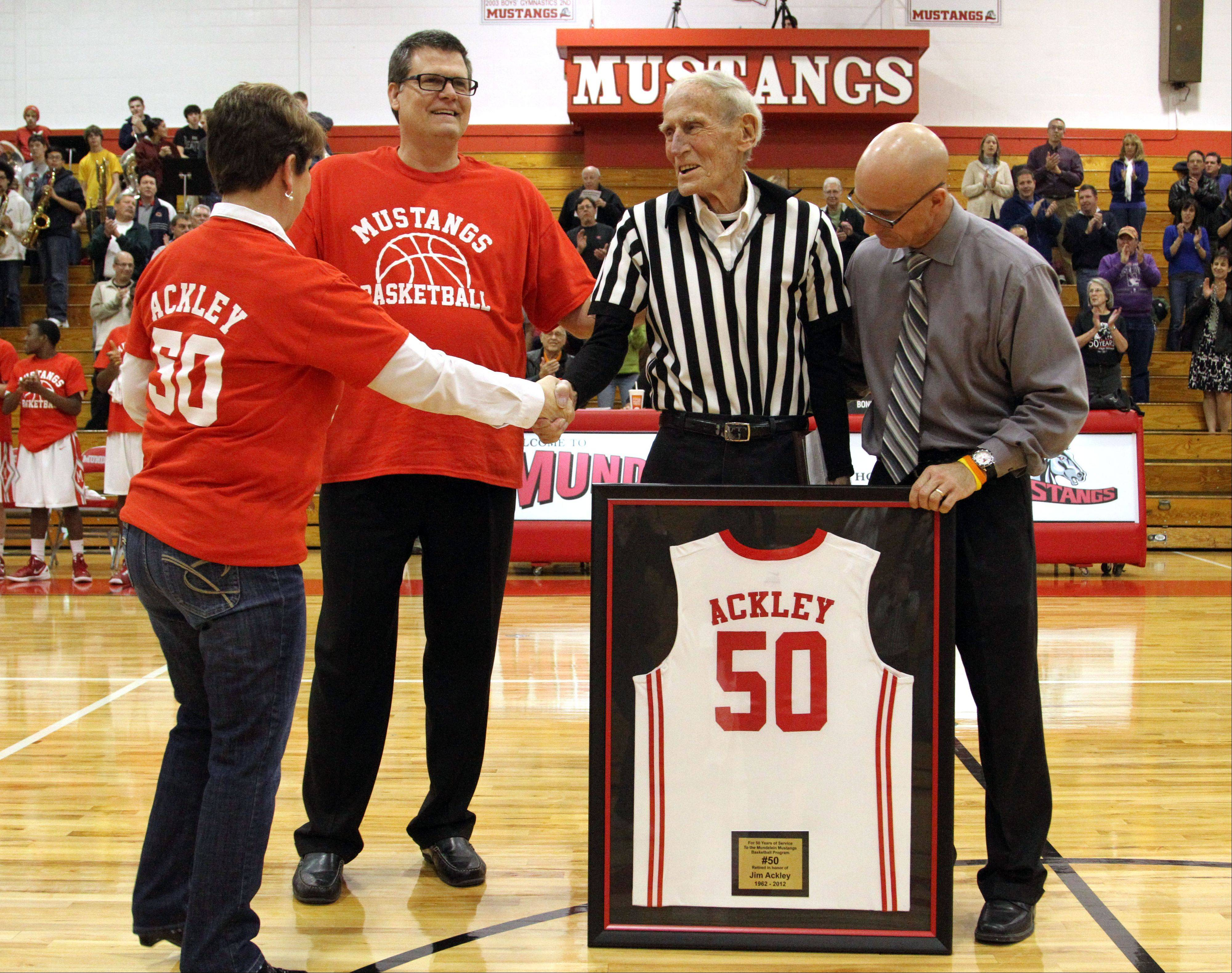 Mundelein basketball scorekeeper Jim Ackley, in stripes, is honored by, from left, superintendent Jody Ware, coach Richard Knar and athletic director Perry Wilhelm for 50 years of service at the school before Tuesday night's game against Lake Zurich.