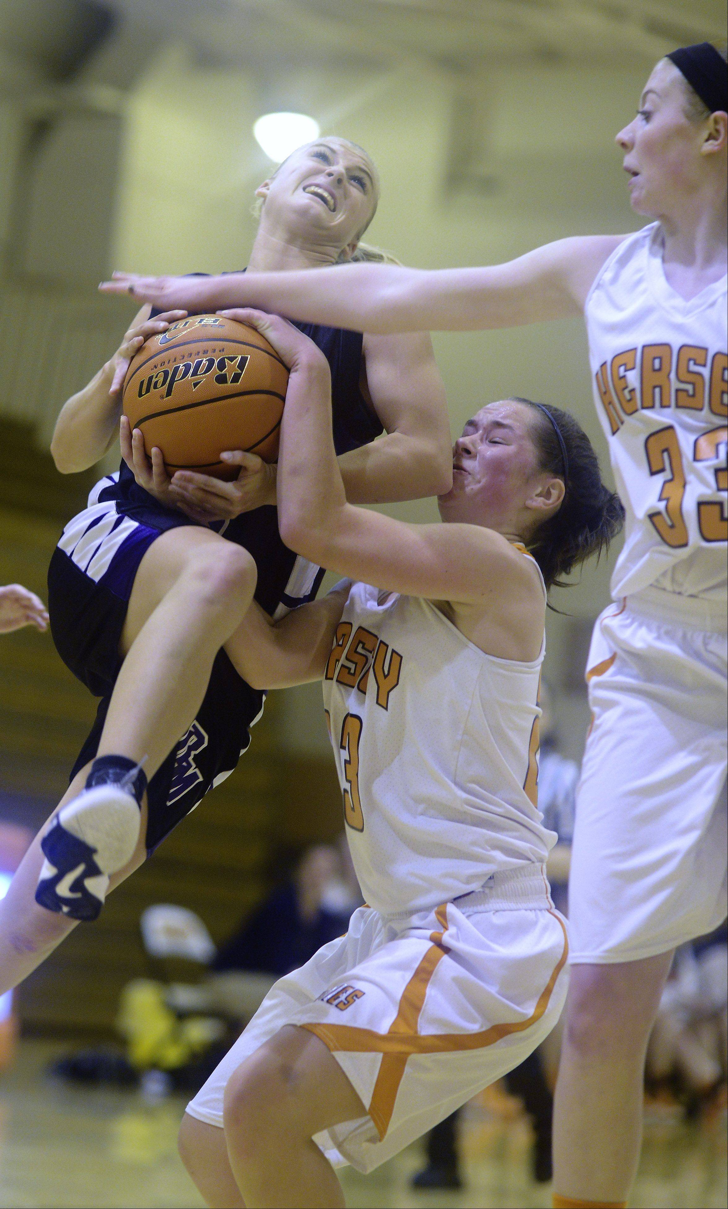 Rolling Meadows' Jackie Kemph, left, gets fouled as she makes a strong move to the basket against Hersey defenders Casey Weyrich, middle, and Ashley Raulli.