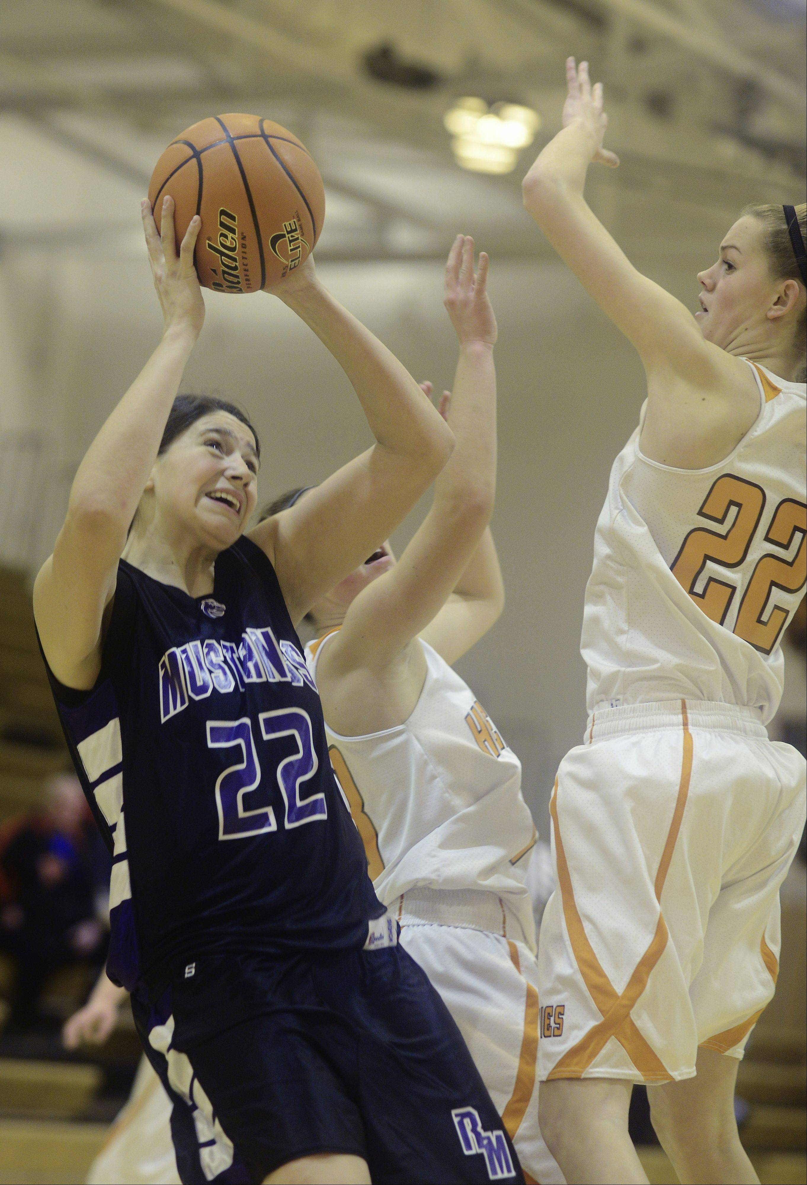 JOE LEWNARD/jlewnard@dailyherald.comRolling Meadows' Ashley Montanez, left, takes a shot against the defense of Hersey's Erica Hill.