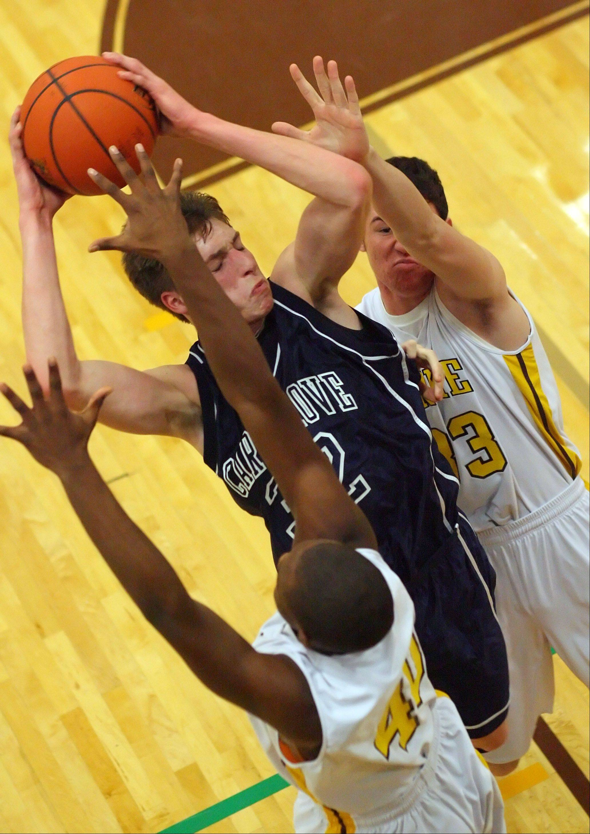 Cary-Grove's Dean Lee, center, drives on Carmel's Chris Duff, left, and Matt Kelly on Wednesday night at Carmel.