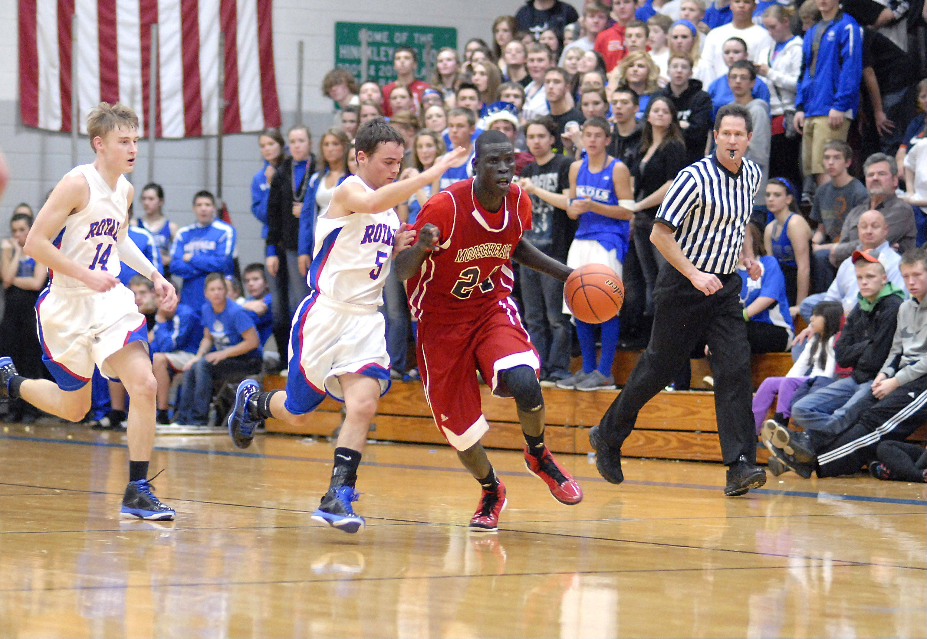 Mooseheart's Mangisto Deng speeds up the court with Hinckley-Big Rock's Bernie Conley in pursuit during the last few minutes of the fourth quarter on Wednesday, December 5.