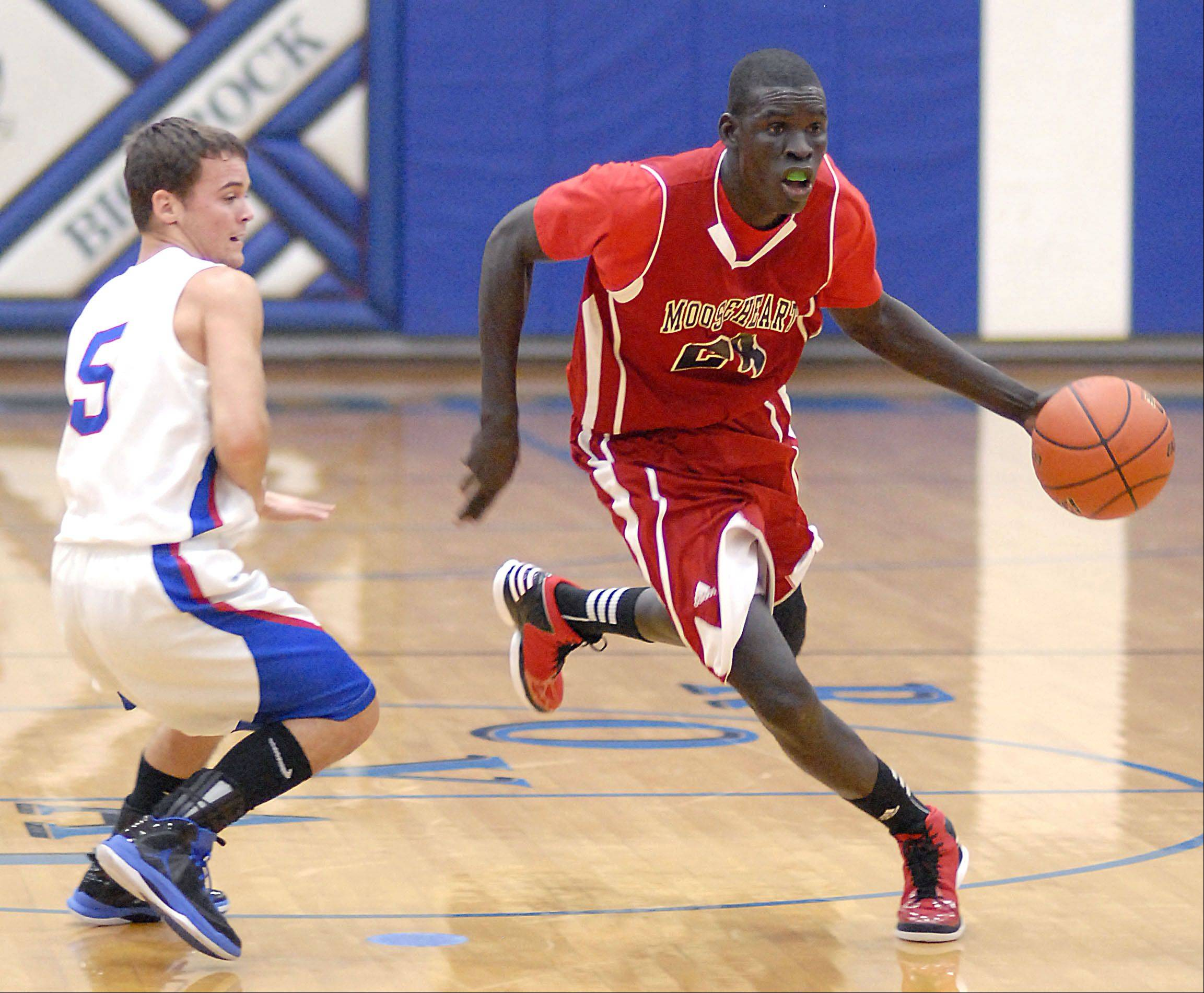 Mooseheart's Mangisto Deng speeds past Hinckley-Big Rock's Bernie Conley in the first quarter.