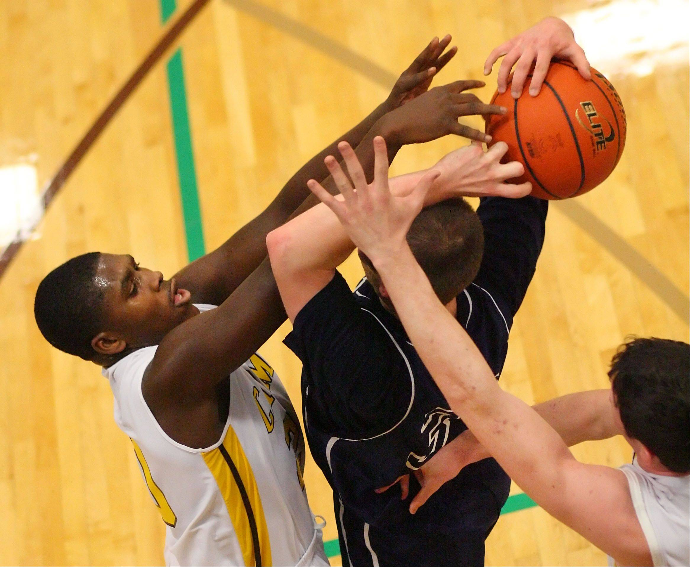 Carmel's Nickai Poyser, left, pressures Cary-Grove's Steve Plazak.