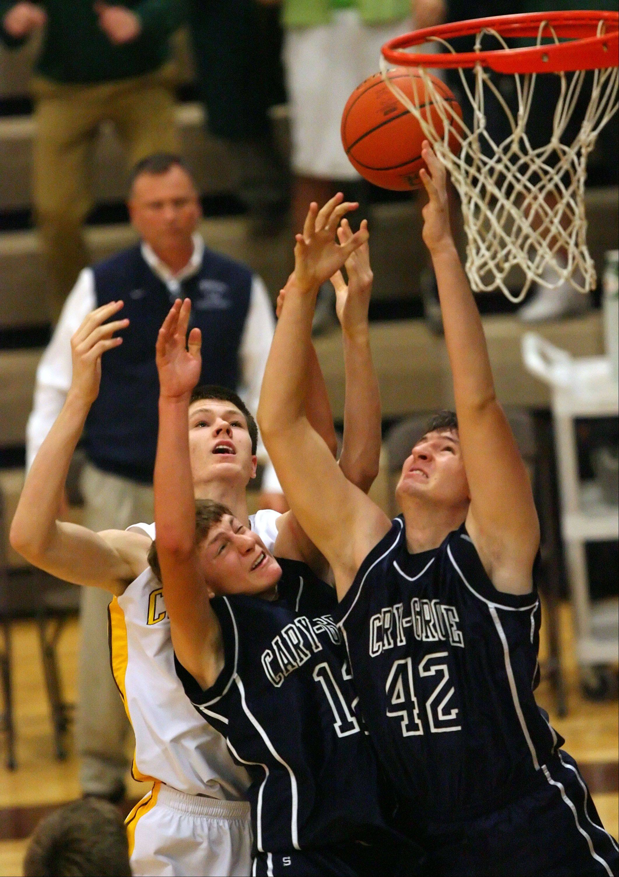 Carmel's Jack George, left, battles for a rebound with Cary-Grove's Jason Gregoire and Alex Crowley, right.