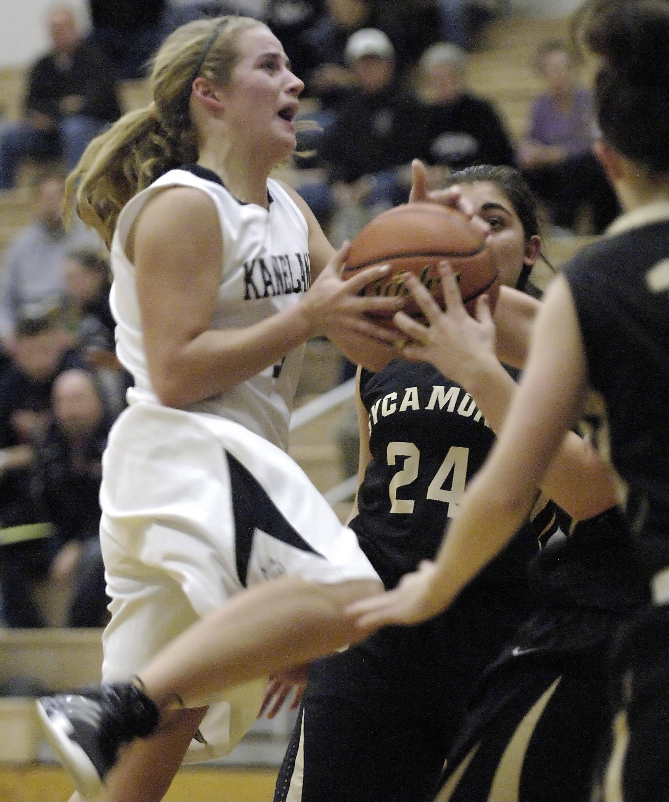 Kaneland's Sarah Grams is fouled as she drives into a group of Sycamore players.