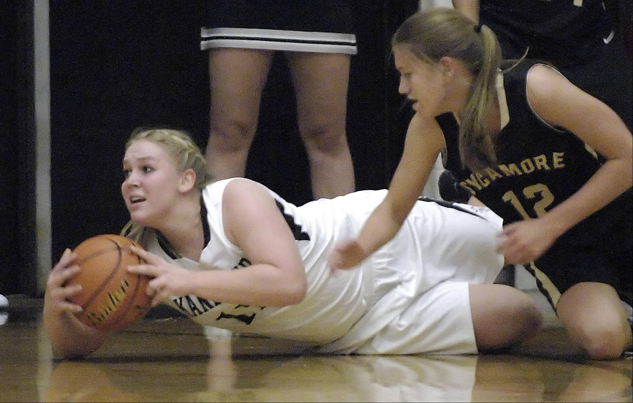 Kaneland's Ashley Prost tries to pass from the floor as Sycamore's Baylee Foresman defends .