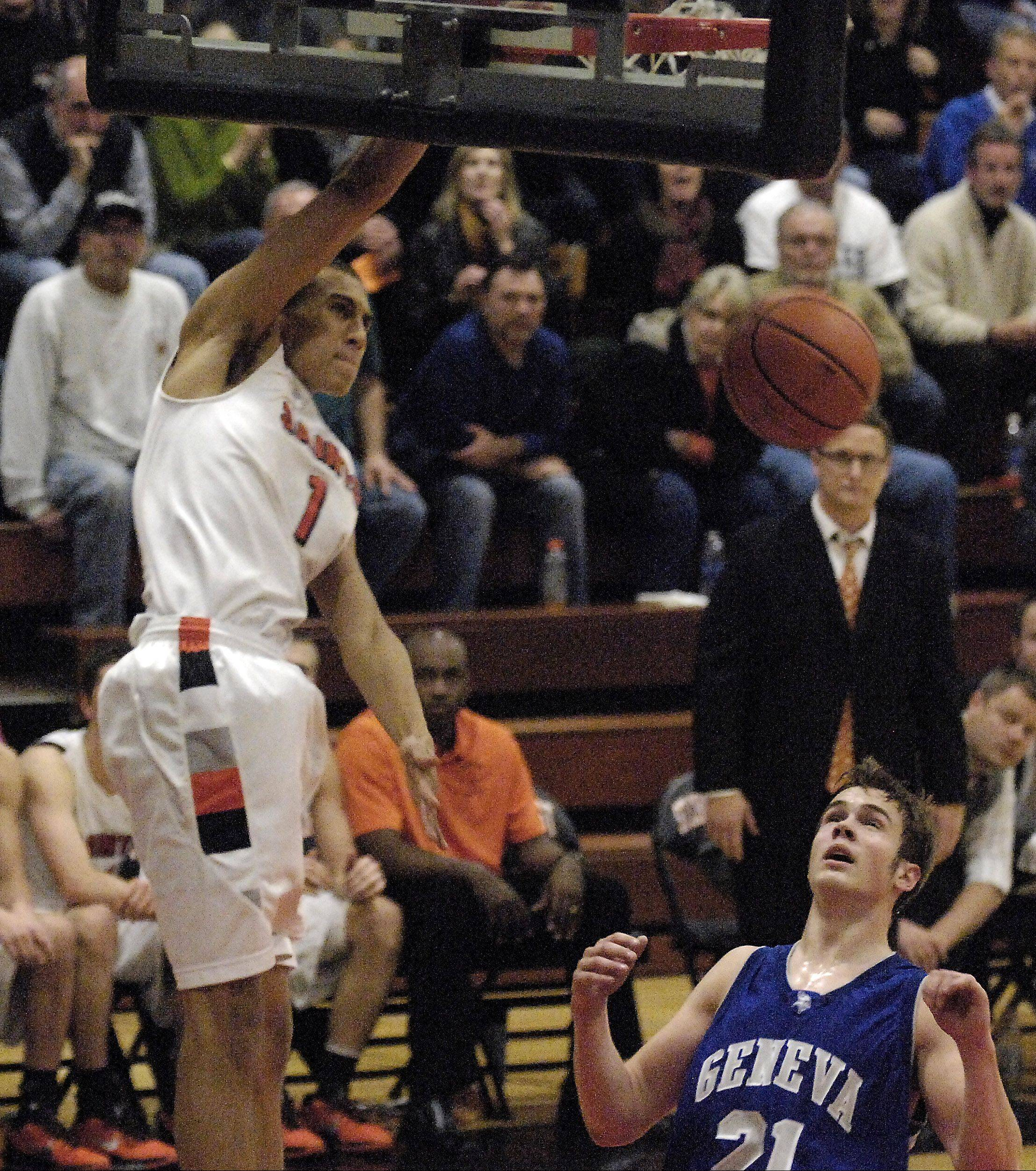 Geneva's Mike Trimble can only watch as St. Charles East's AJ Washington throws down a dunk.