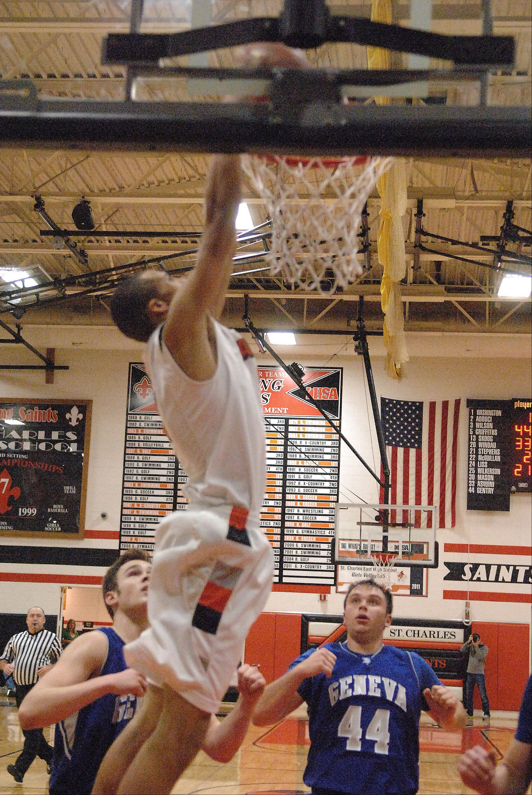 St. Charles East's AJ Washington goes high to slam an alley-oop pass from Dom Adduci Friday against Geneva.