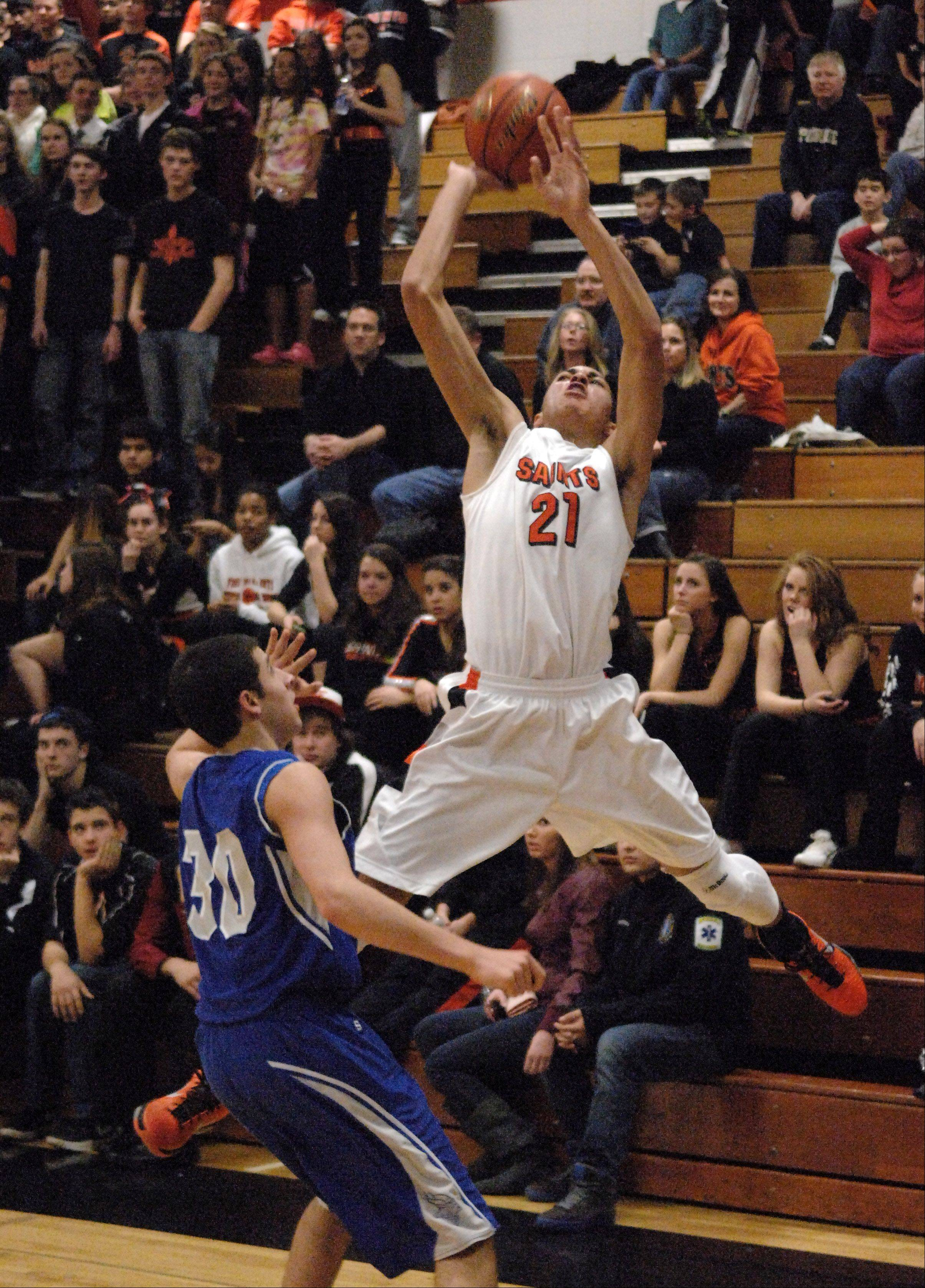 St. Charles East's Kendall Stephens draws a foul while attempting a 3-pointer against Geneva.