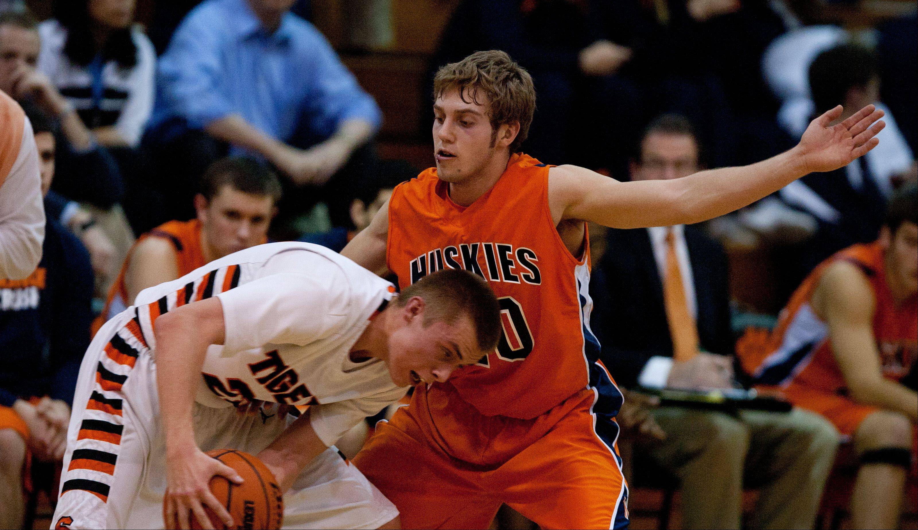 Wheaton Warrenville South's Michael Kramer, left, lowers his head against a Naperville North defender during boys basketball action in Wheaton.