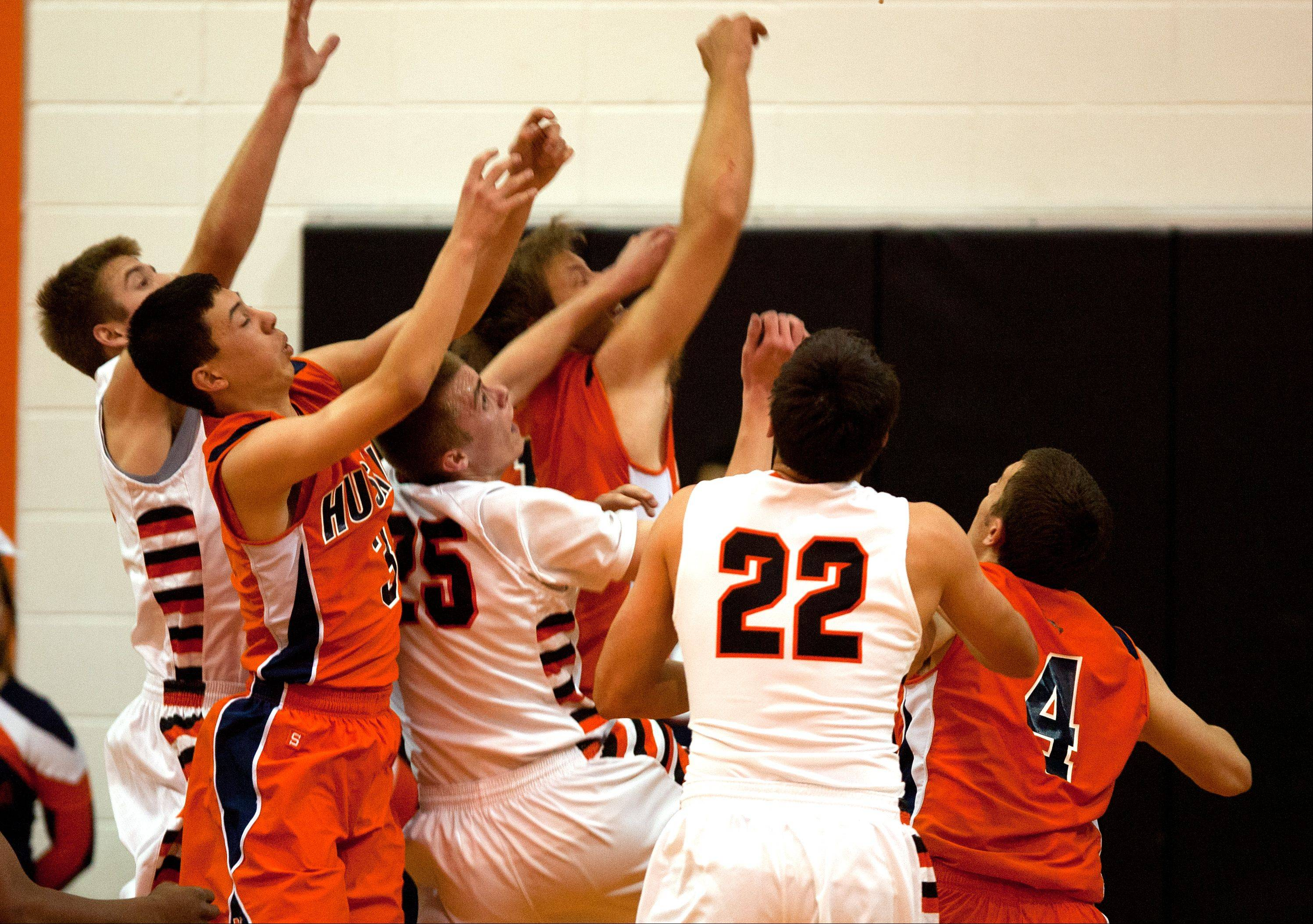 Naperville North and Wheaton Warrenville South players fight for a rebound during boys basketball action in Wheaton.