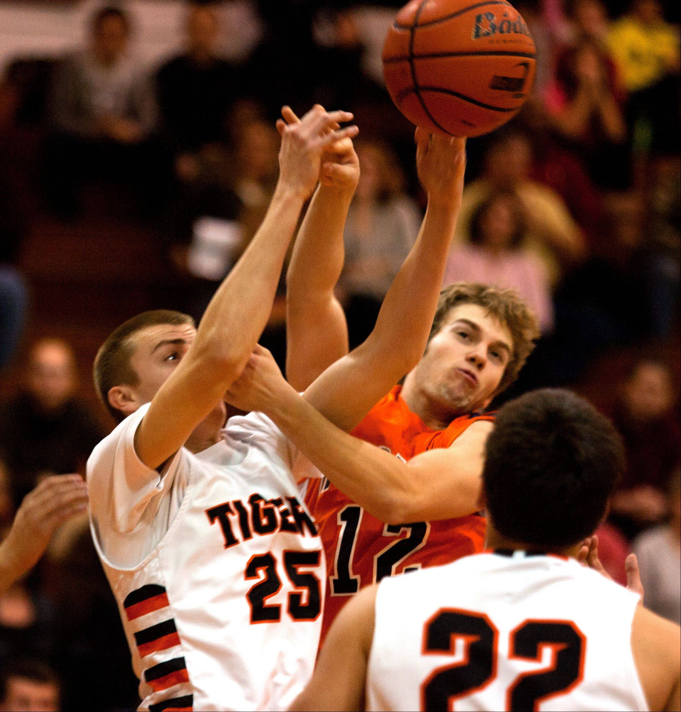 Wheaton Warrenville South's Michael Kramer (25), battles Naperville North's Bryan LoLordo (12), during boys basketball action in Wheaton.