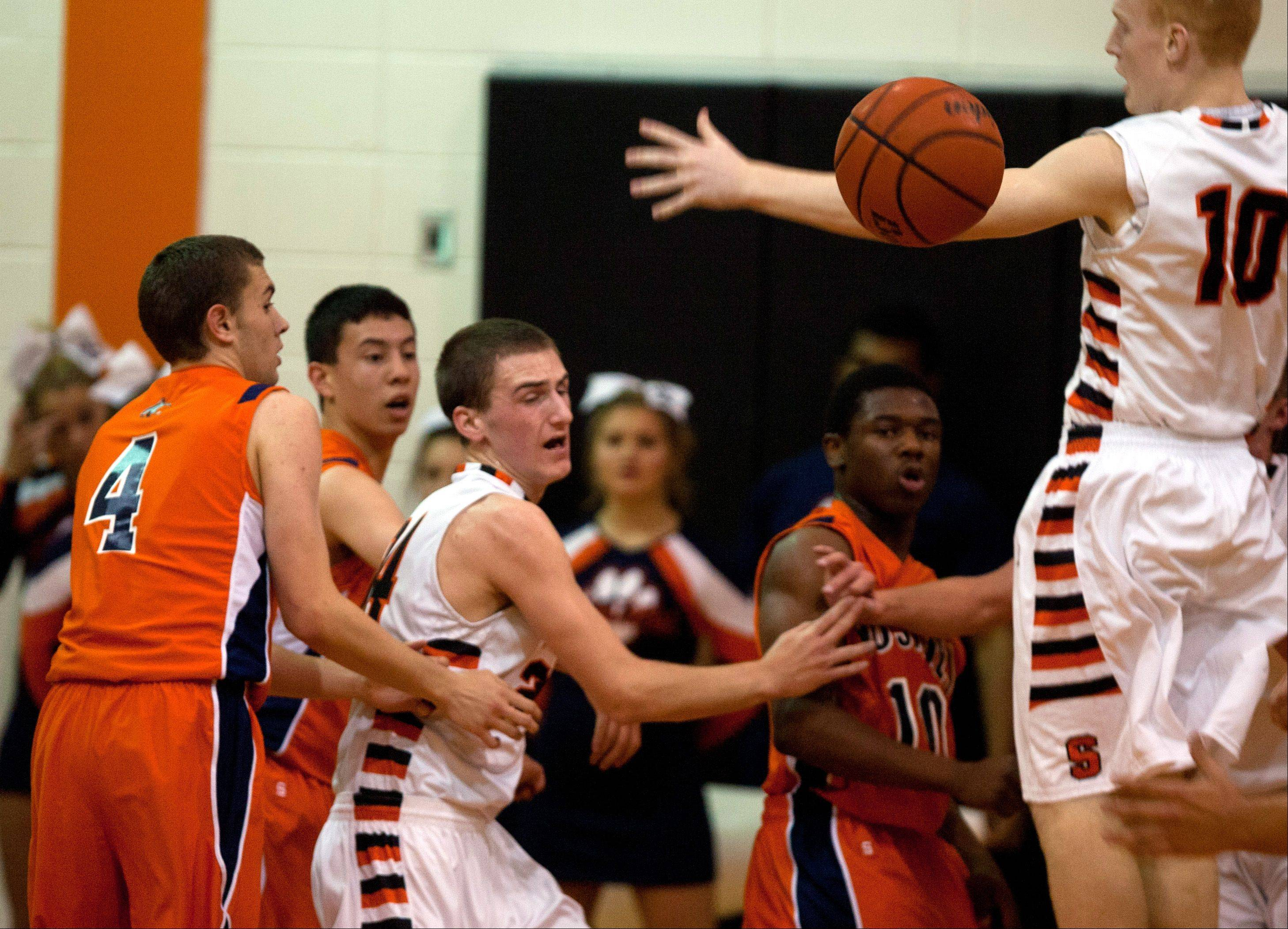 Wheaton Warrenville South's Ryan Graham (10), looks to block a pass against Naperville North during boys basketball action in Wheaton.