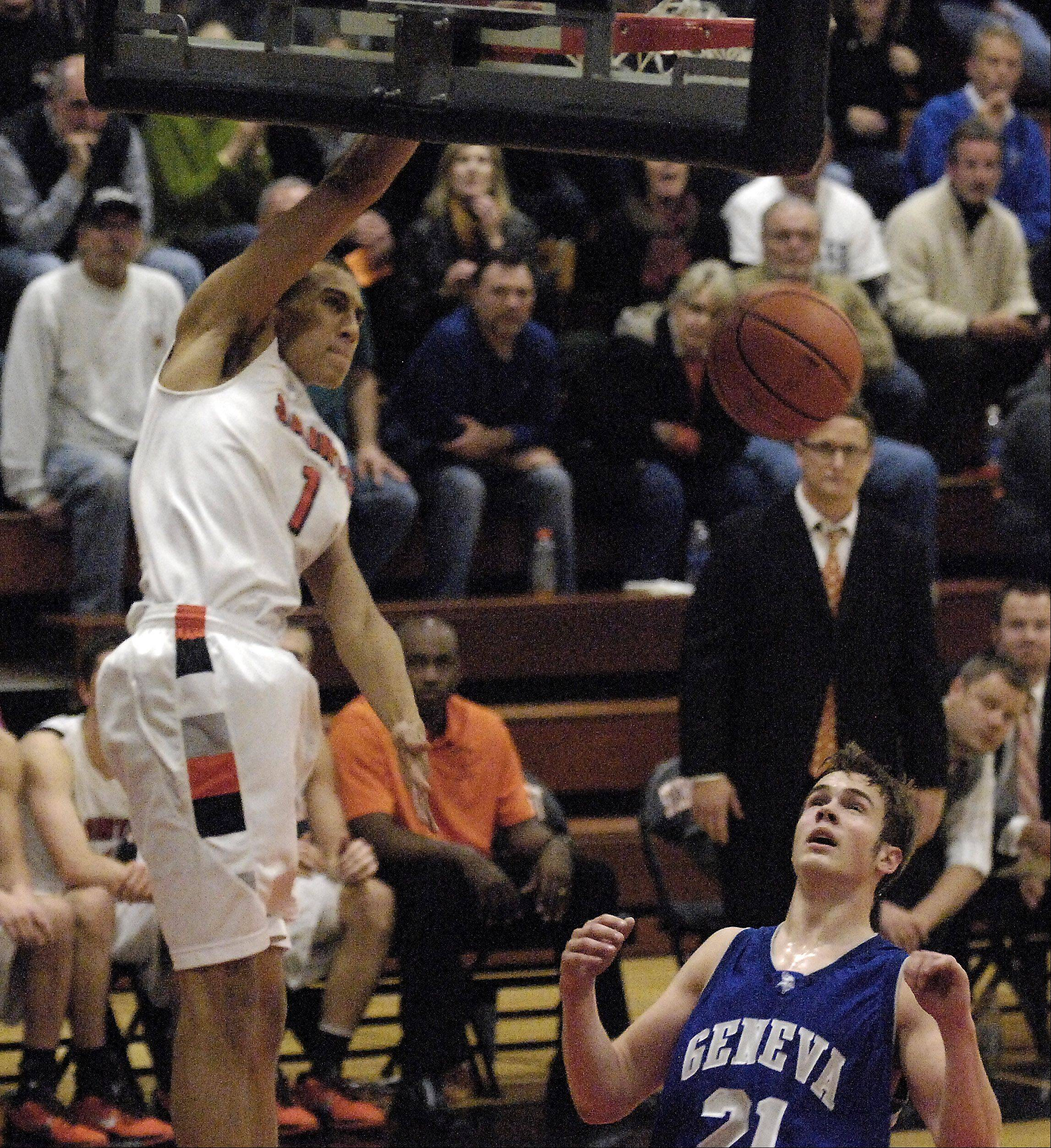 Geneva's Mike Trimble watches as St. Charles East's AJ Washington throws down a dunk.