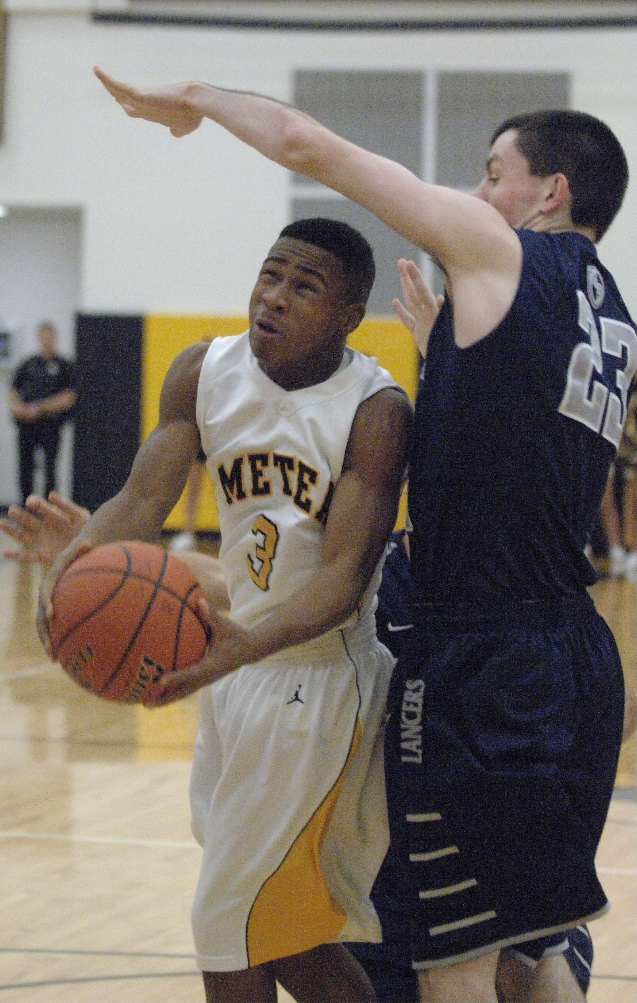 Bryson Oliver,left, of Metea Valley takes a shot as Sean Moore of Lake Park blocks.