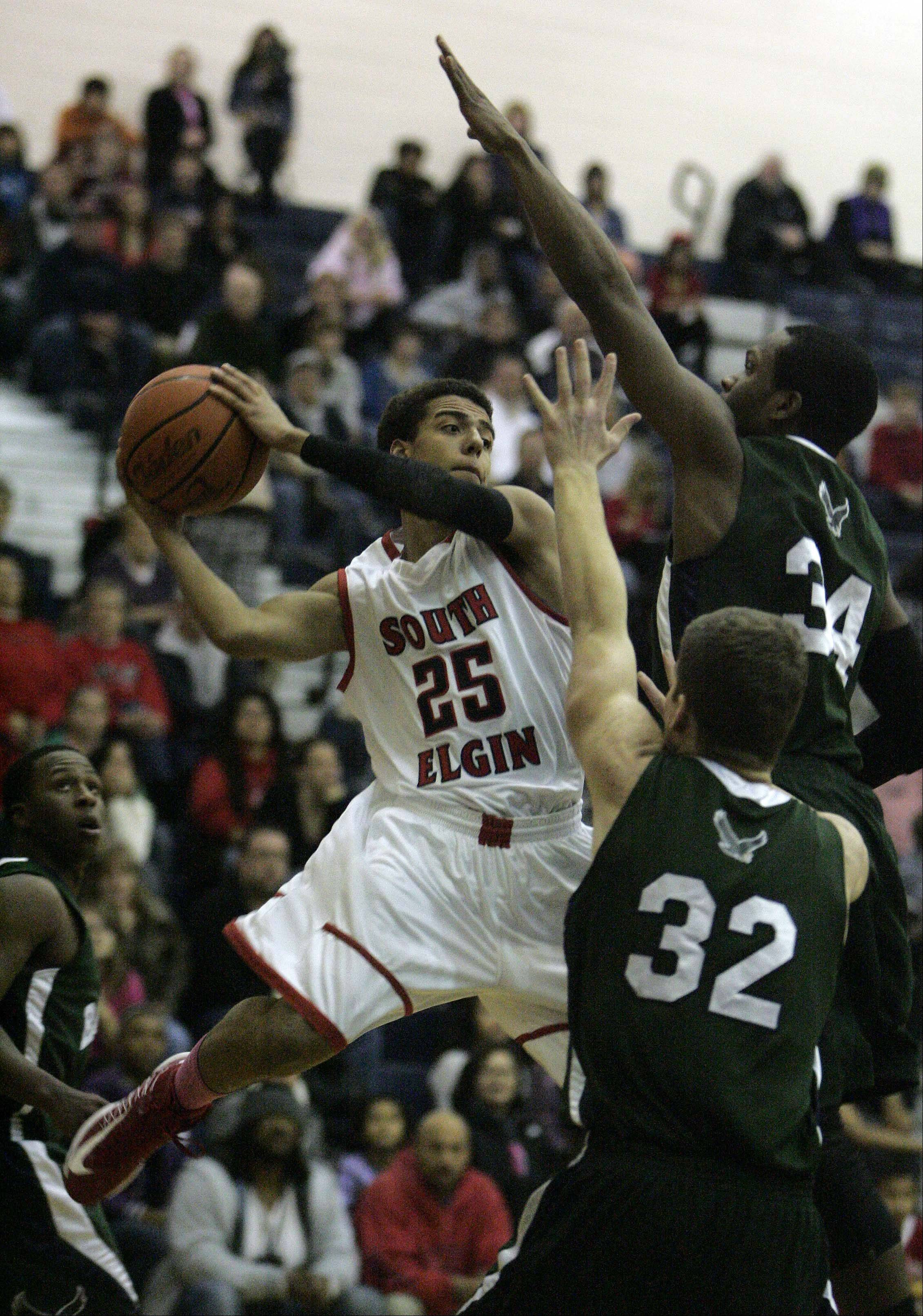 South Elgin guard Darius Wells goes to the hoop past Bartlett guard Lance Whitaker and Mitch Reid .