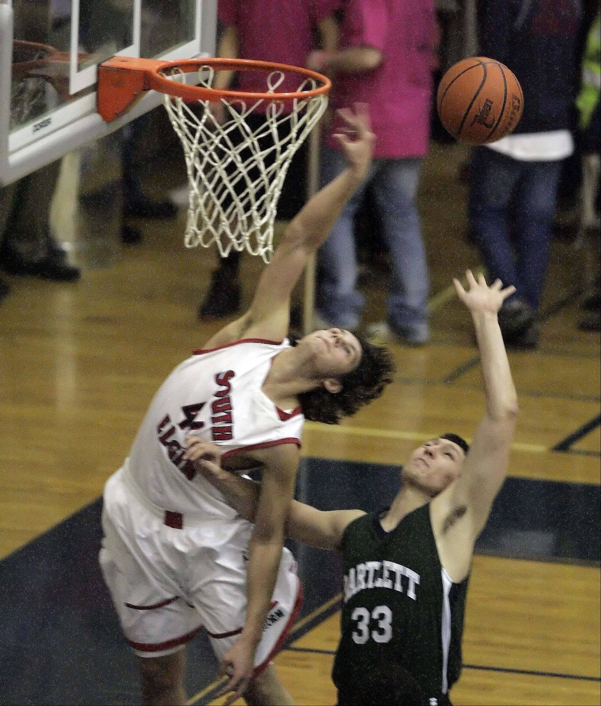 South Elgin's Ryne Lundy is fouled on his way to the hoop by Bartlett forward Brian Triphahn .