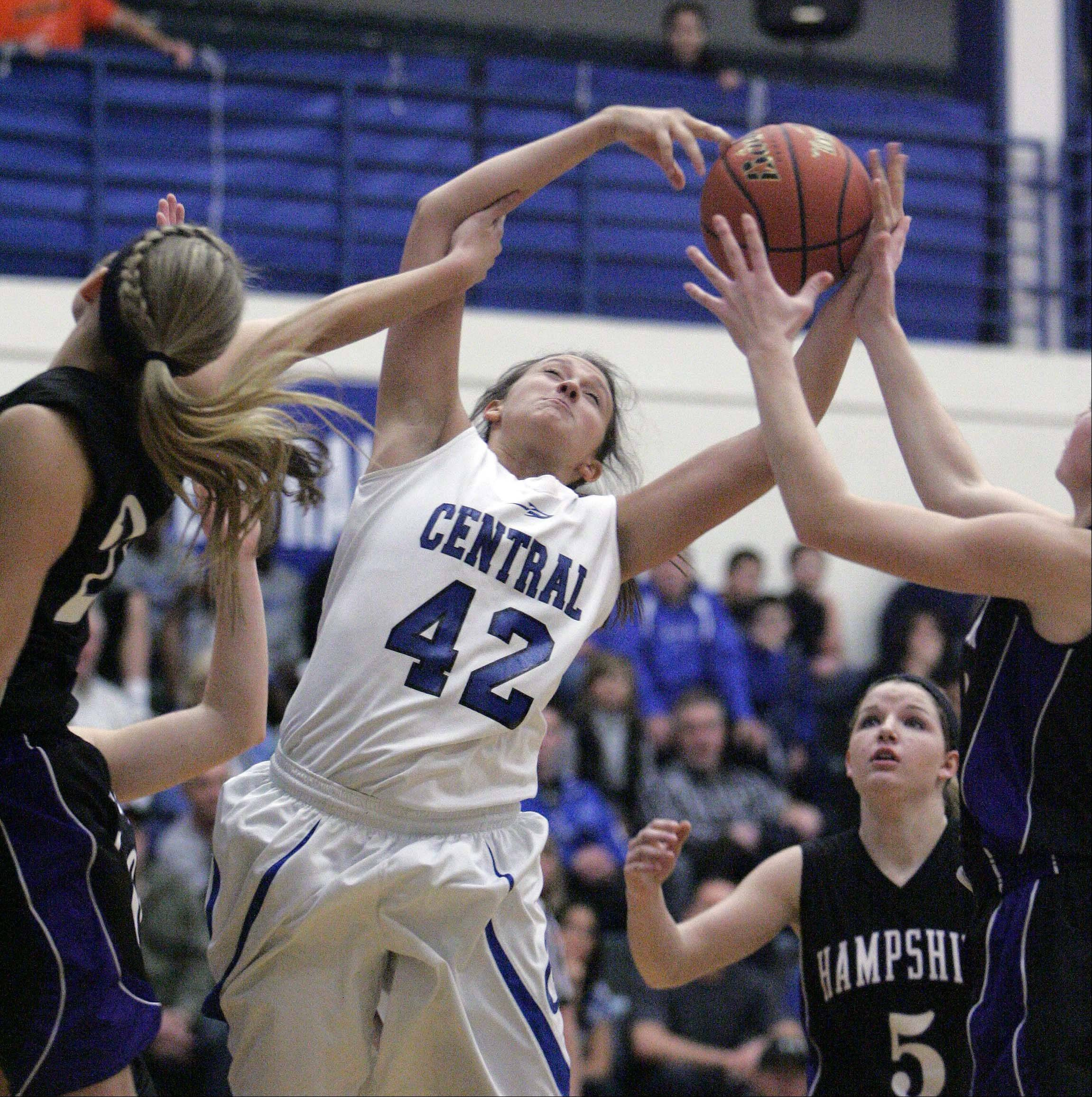 Burlington Central's Alison Colby (42) rips down a rebound during the Rockets' 48-37 win over Hampshire at Burlington Central Saturday.
