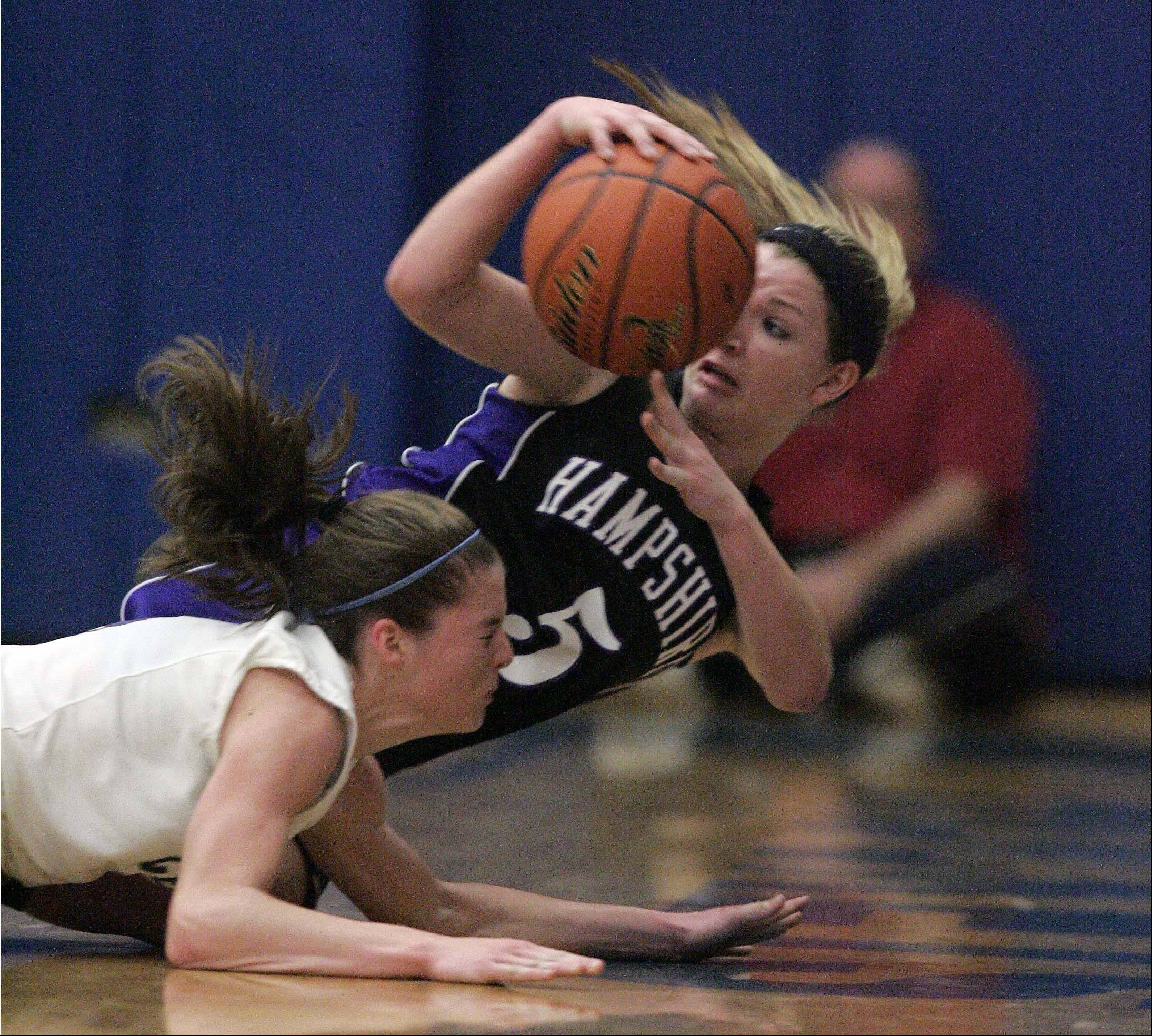 Hampshire guard Sara Finn (5) dives for a loose ball as Burlington Central's Kayla Ross (4) tries to gain control also during Hampshire at Burlington Central girls basketball Saturday December 8, 2012.