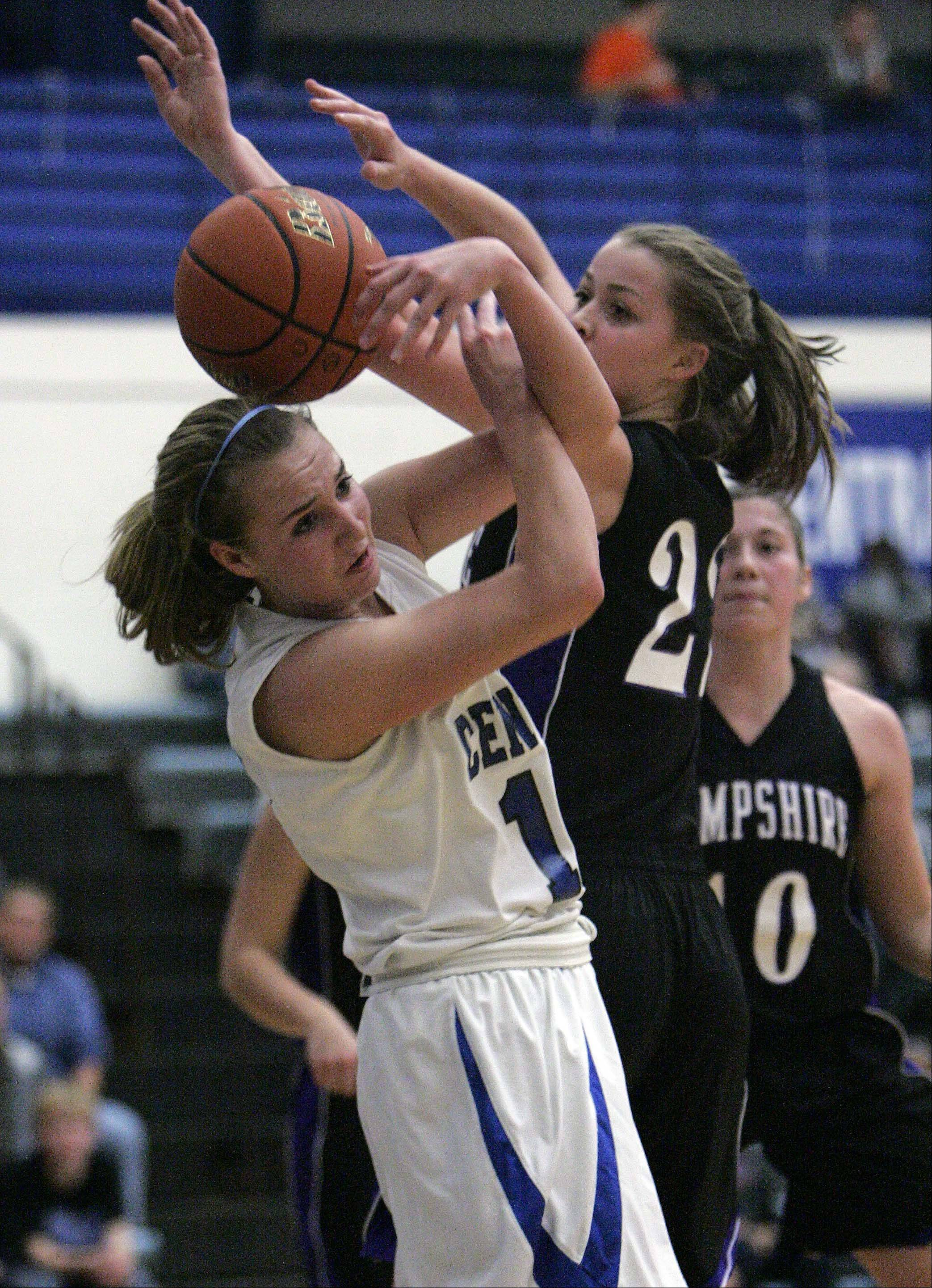 Burlington Central's Shelby Holt (12) and Hampshire c/f Emma Beniot (22) get tangled up trying to grab a loose rebound during Hampshire at Burlington Central girls basketball Saturday December 8, 2012. 12 22