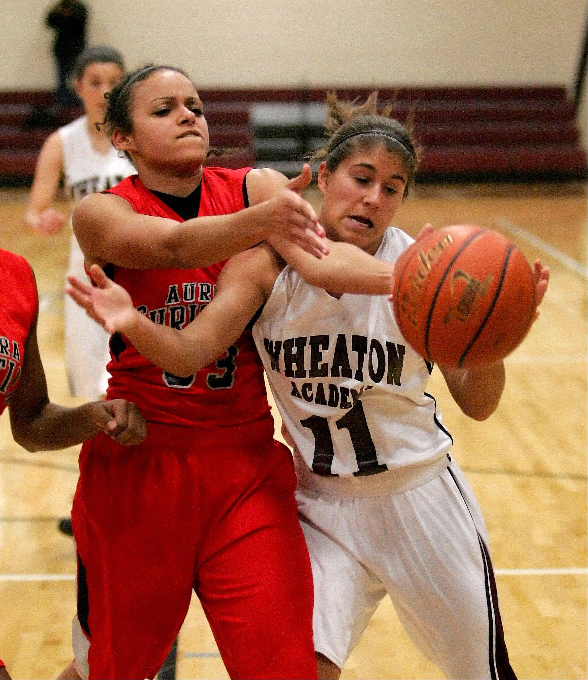 Alyssa Andersen, left, of Aurora Christian and Marissa Gagliano of Wheaton Academy, right, go after a loose ball during girls basketball action in West Chicago on Monday.