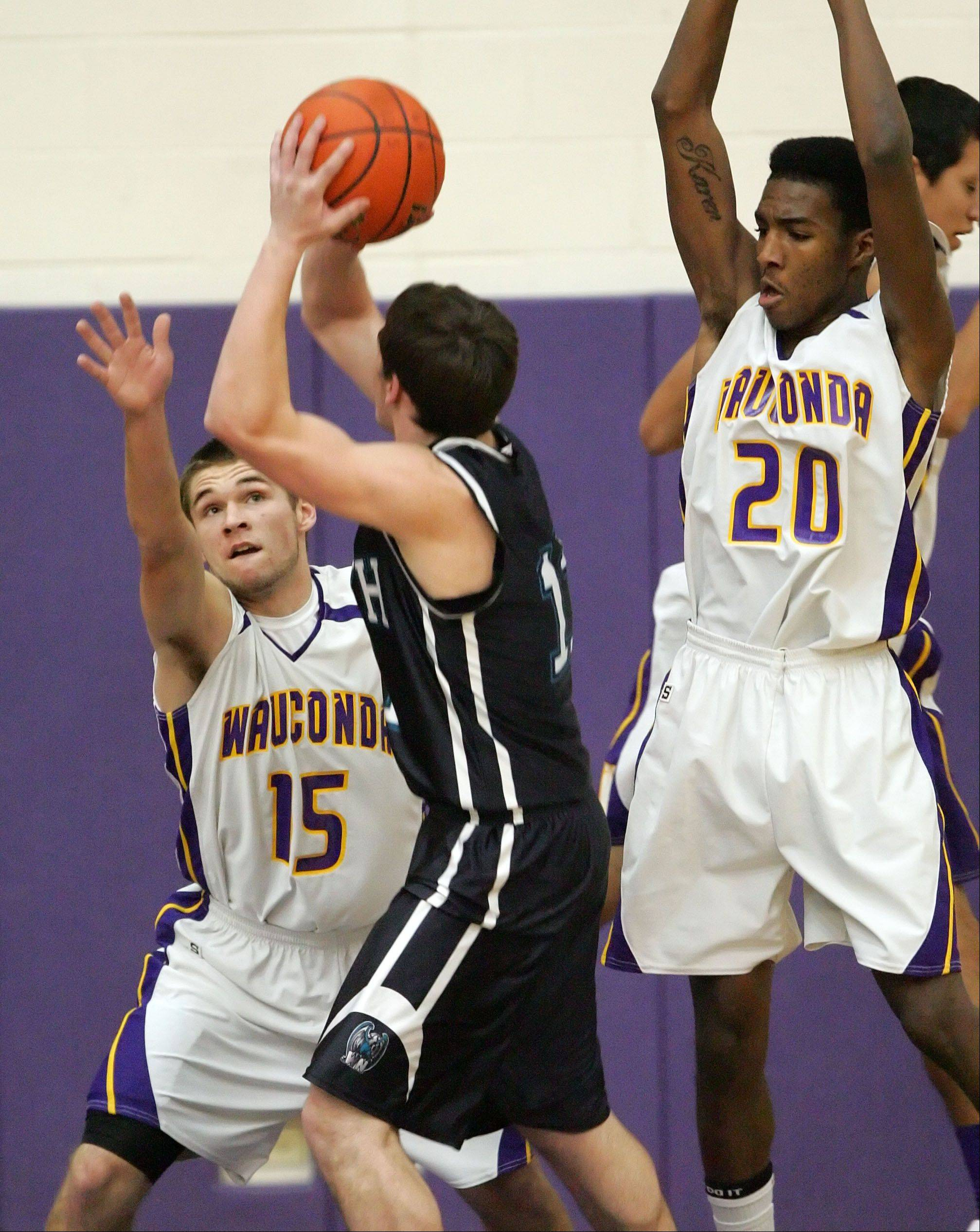 Wauconda's Keith Blomberg, left, and Devon King defend against Woodstock North's Steven Whiting.