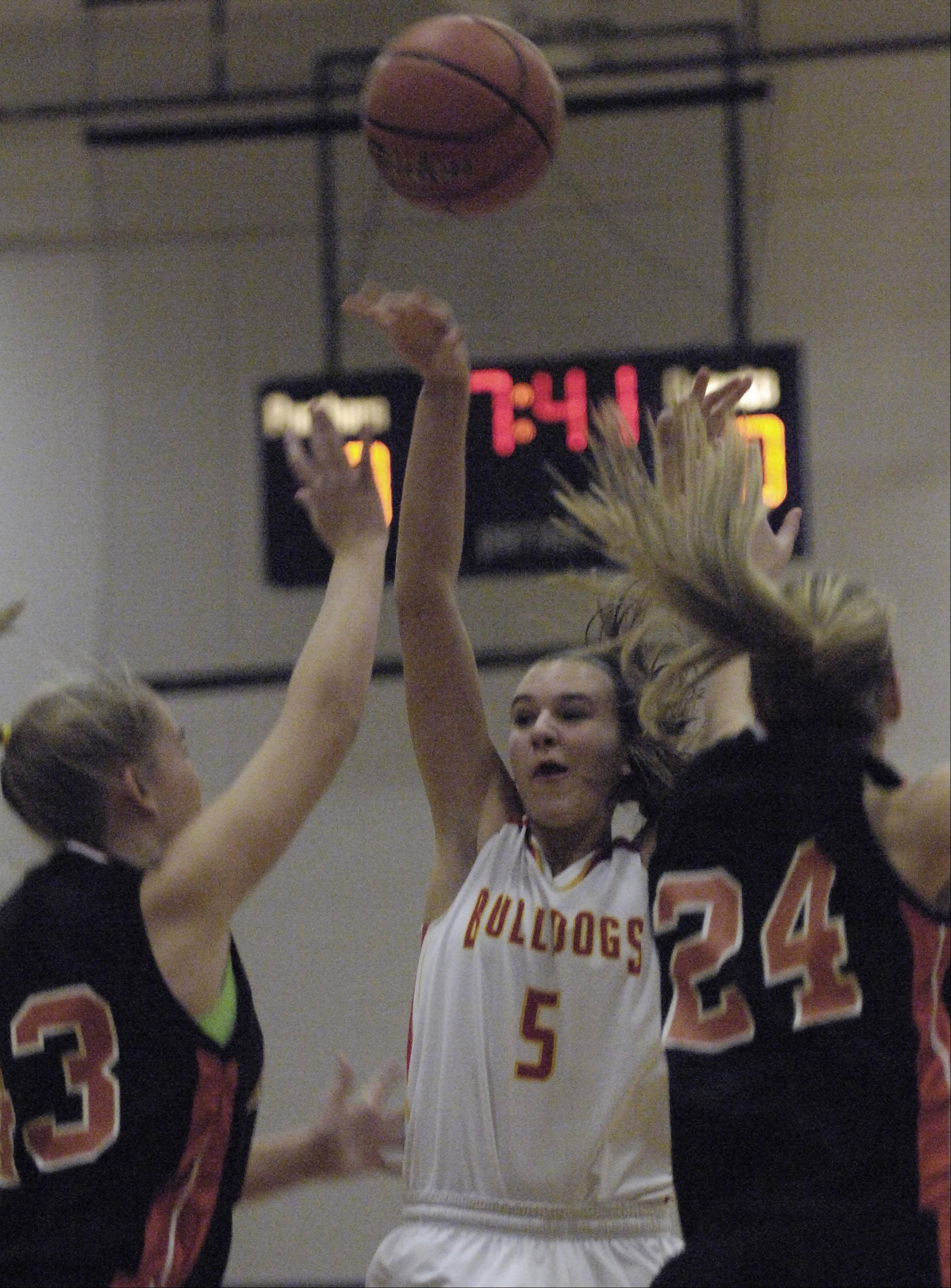 Batavia's Liza Fruendt shoots between Minooka's Alexa Hinkleman and Larissa McLemen at the Oswego High School Holiday Classic Monday.