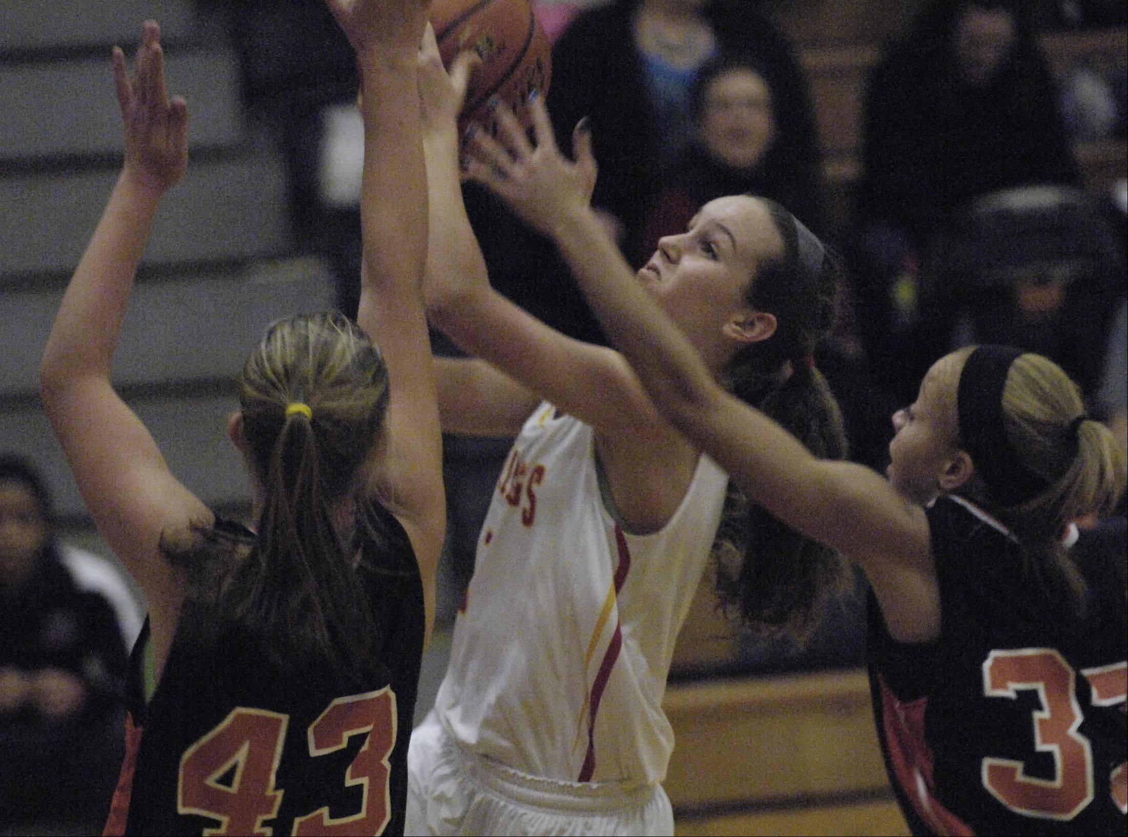Batavia's Bethany Orman shoots between Minooka's Sydney Arlis and Sydney Lilly.