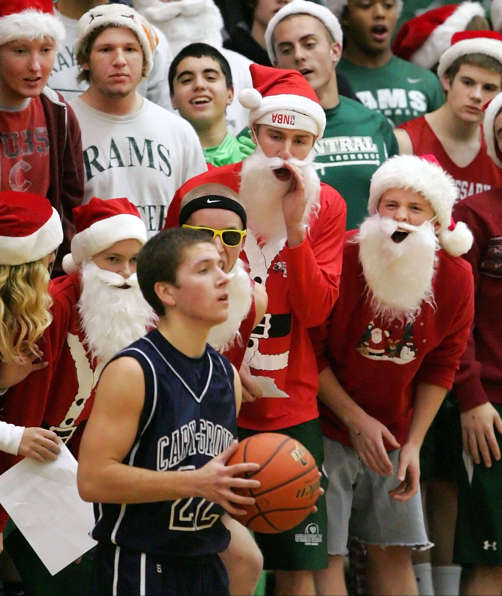 Grayslake Central fans dressed in Santa costumes jeer Cary-Grove's Matt Motzel as he inbounds the ball Tuesday night at Grayslake Central.