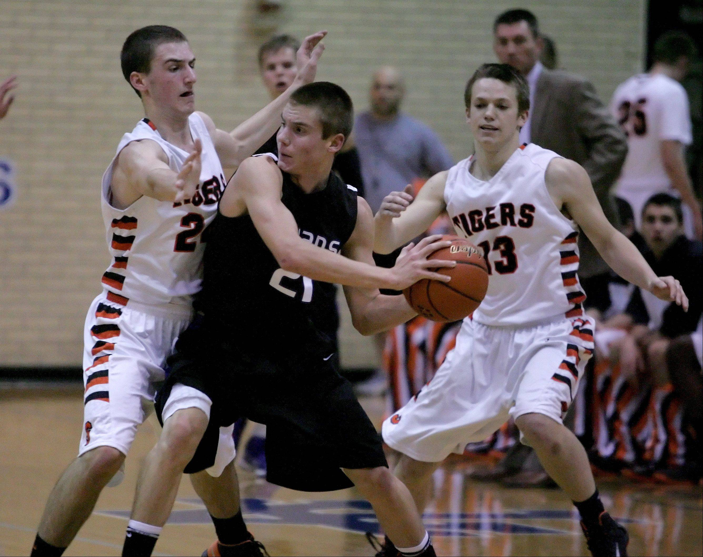 David Henson of Downers Grove North, looks for room to pass as Matt Kienzle, left and Adam Rogers, right, of Wheaton Warrenville South, defend in boys basketball action in Addison on Tuesday.