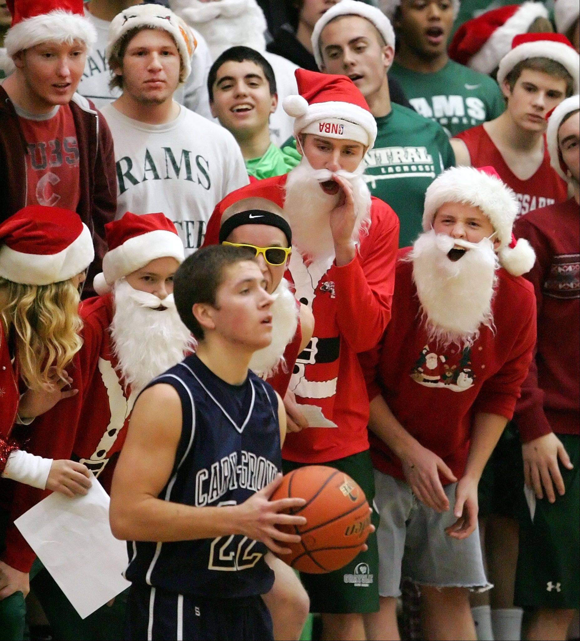 Grayslake Central fans dressed in Santa costumes jeer Cary-Grove's Matt Motzel as he inbounds the ball.