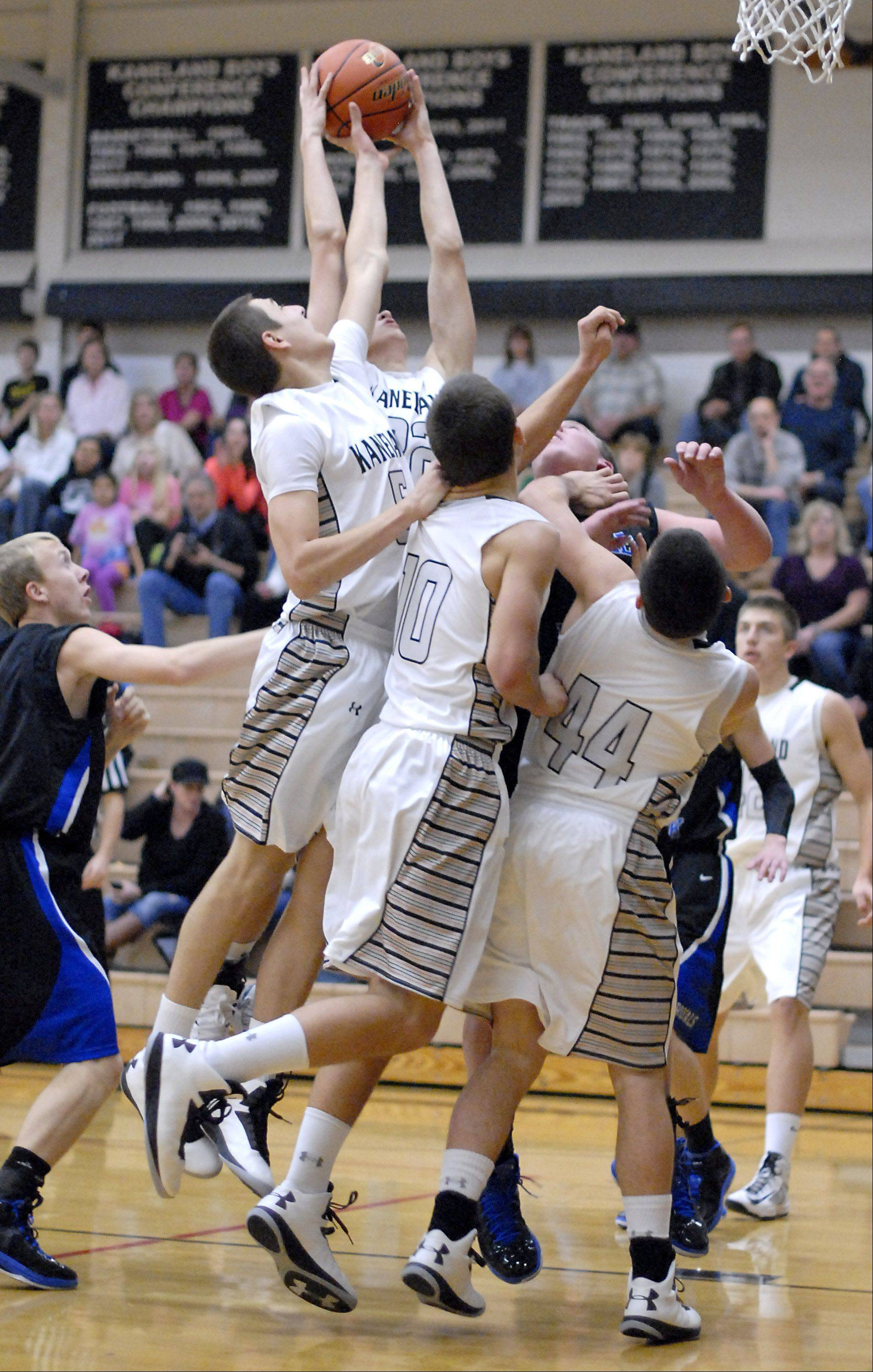 Kaneland's John Pruett and Dan Miller reach for a rebound in the first quarter.