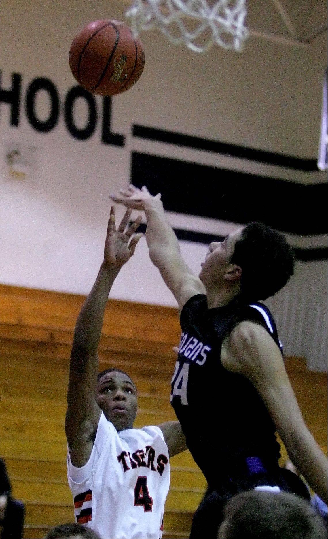Keishawn Watson of Wheaton Warrenville South shoots the ball over Nick Norton of Downers Grove North.