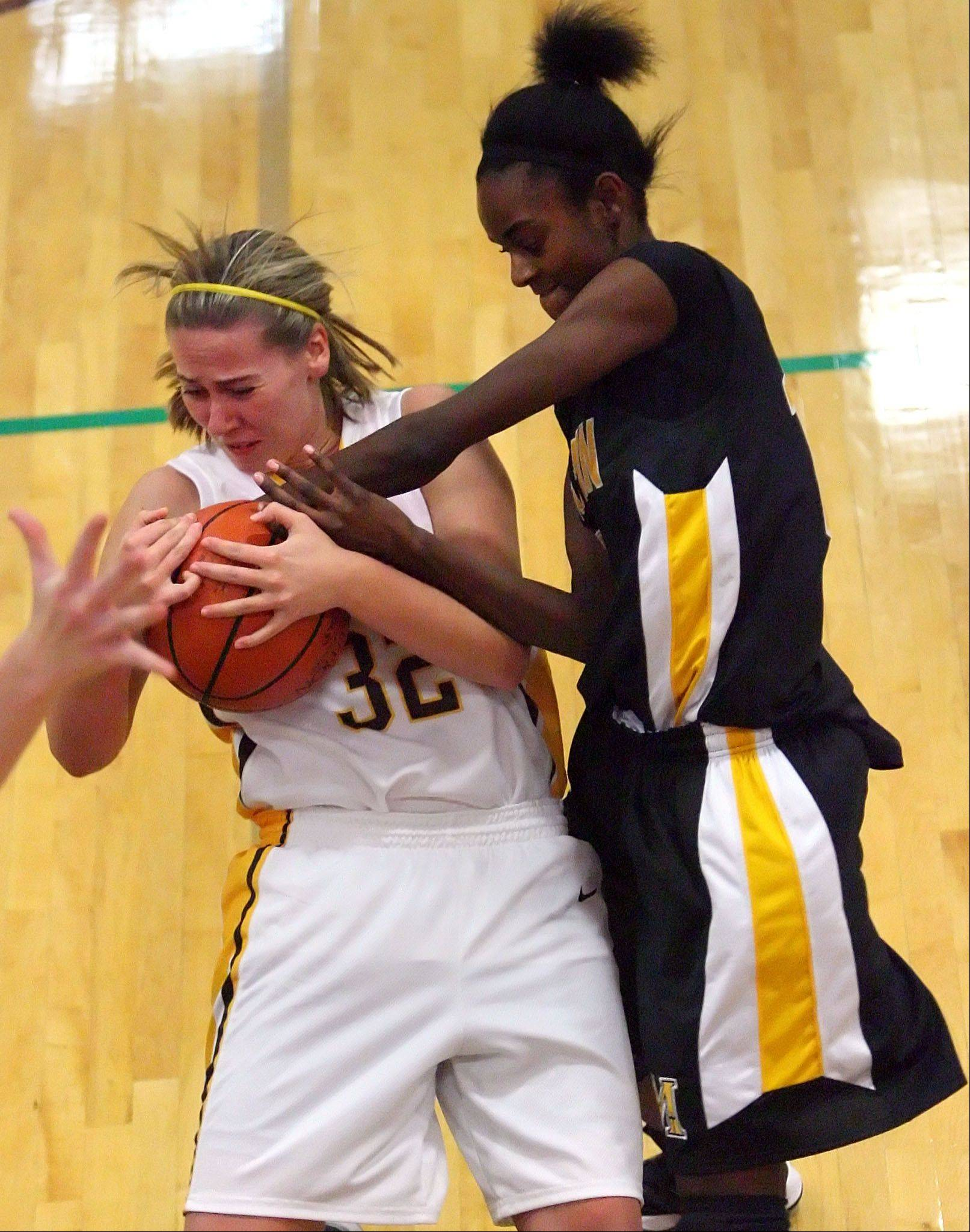Carmel Catholic's Emma Rappe, left, battles for a rebound with Marian Catholic's Kauai Bradley .