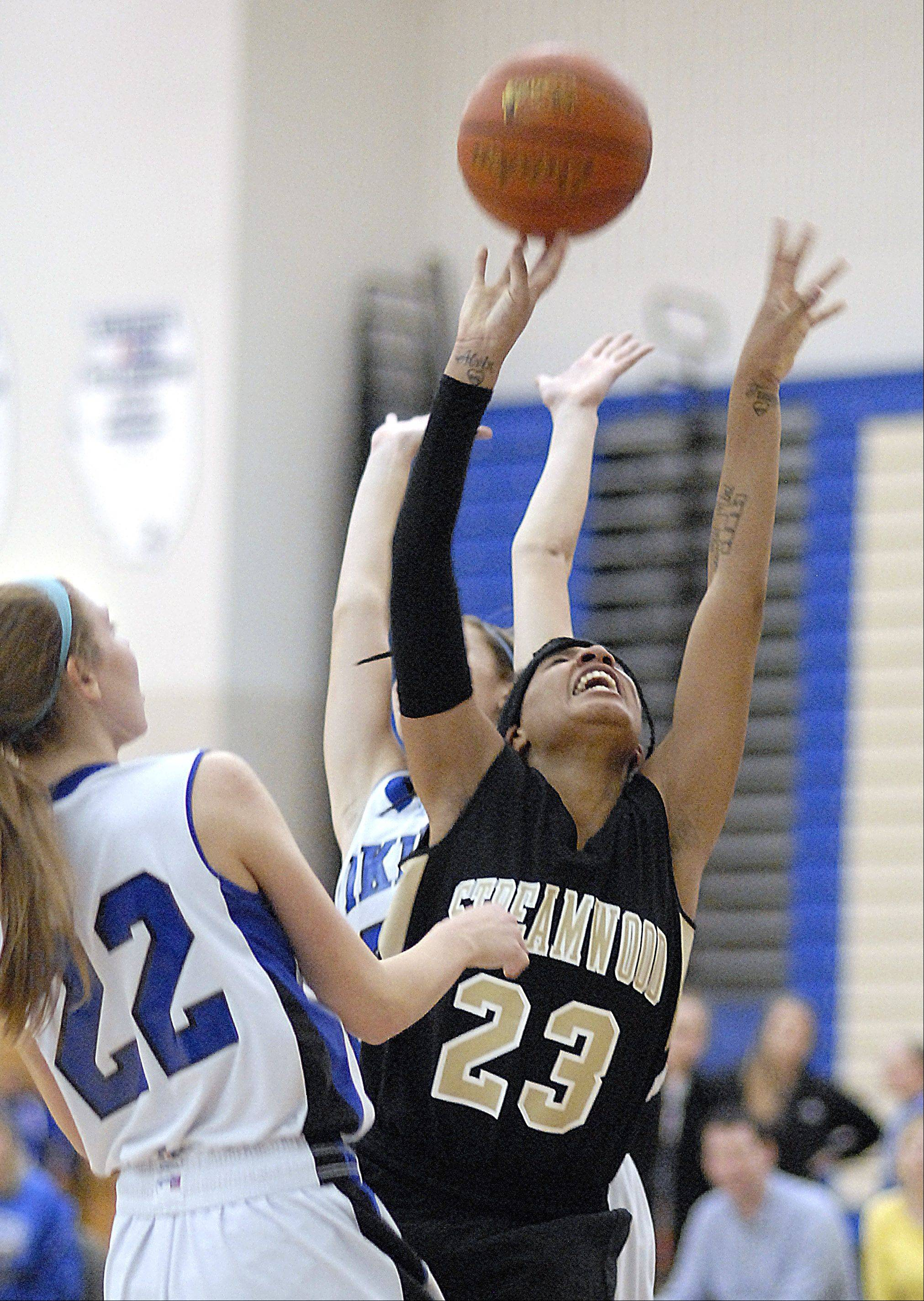 Streamwood's Deja Moore and Geneva's Madeline Dunn fight for a Sabres rebound in the second quarter on Wednesday, December 12.