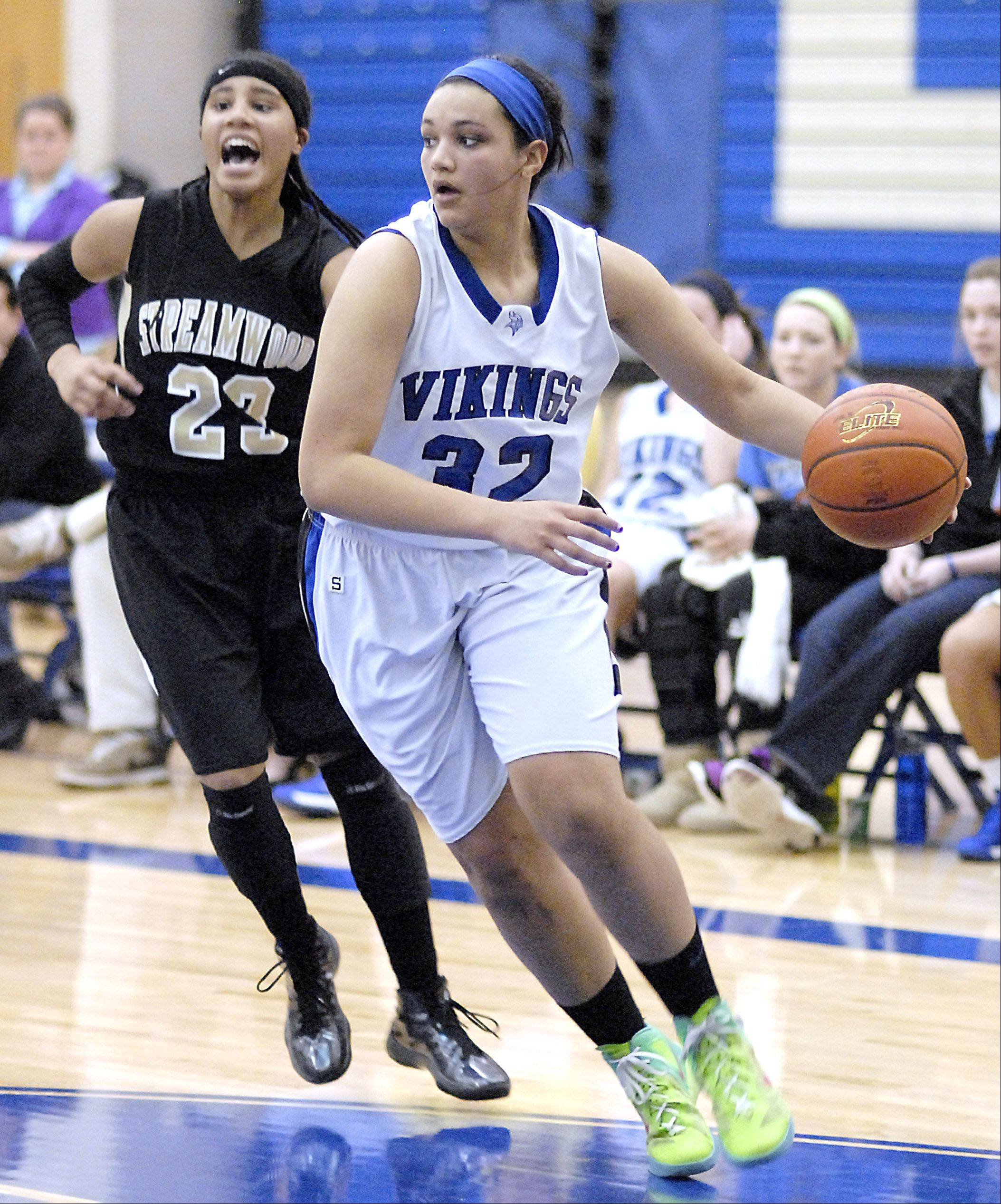 Geneva's Sidney Santos is trailed by Streamwood's Deja Moore near the basket in the fourth quarter.