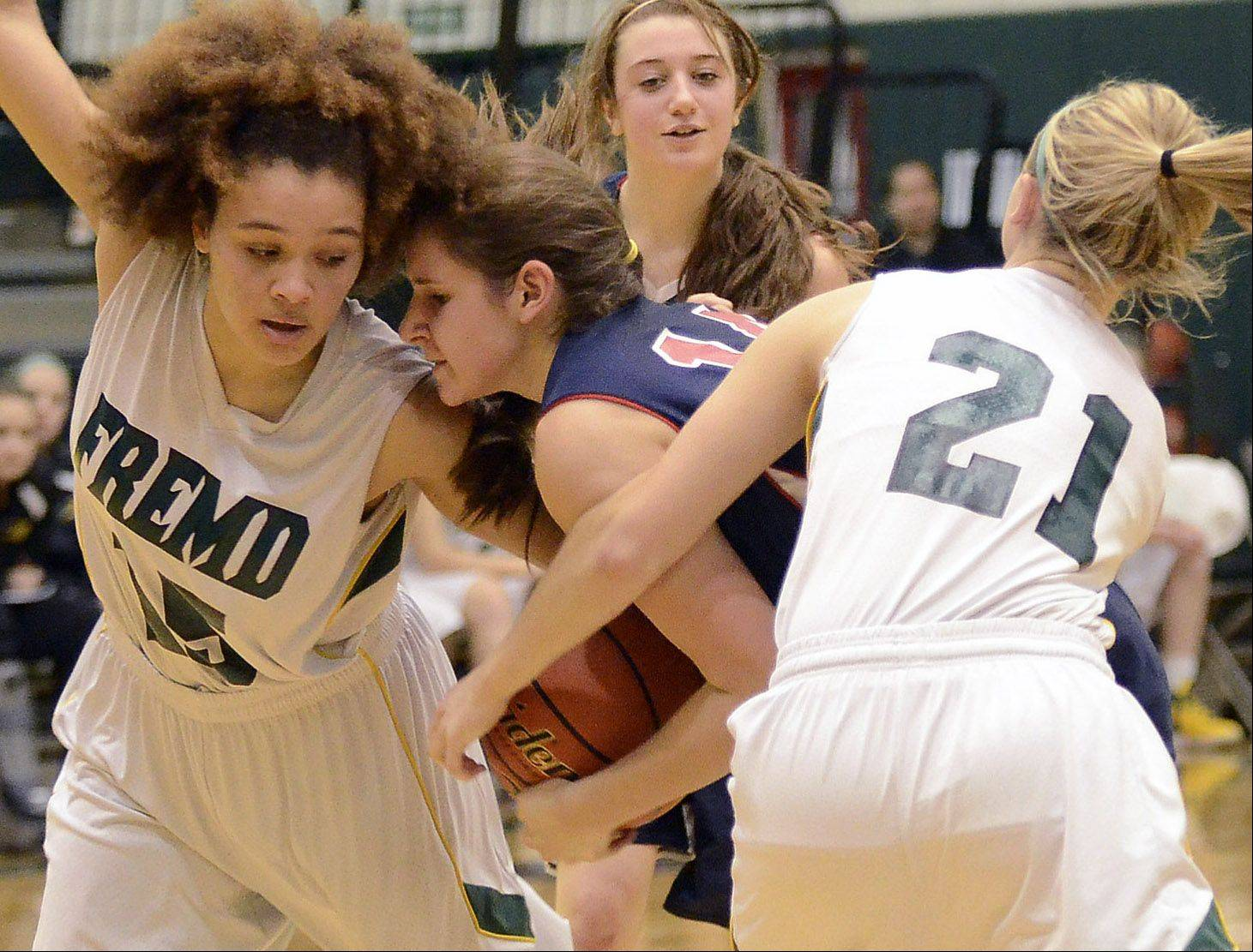 Fremd's Bernie Williams (15), left, and Ashley McConnell (21) tie up Conant's Sarah Mazurek (14) during MSL West play Thursday in Palatine.