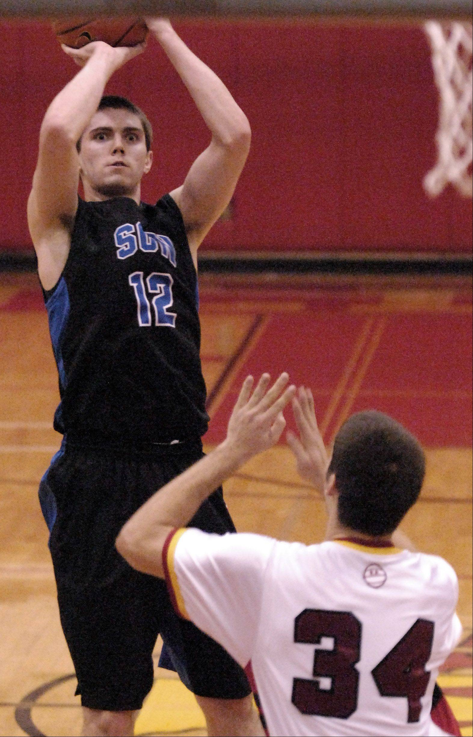 St. Charles North's Quinten Payne shoots and scores from the outside against Batavia.