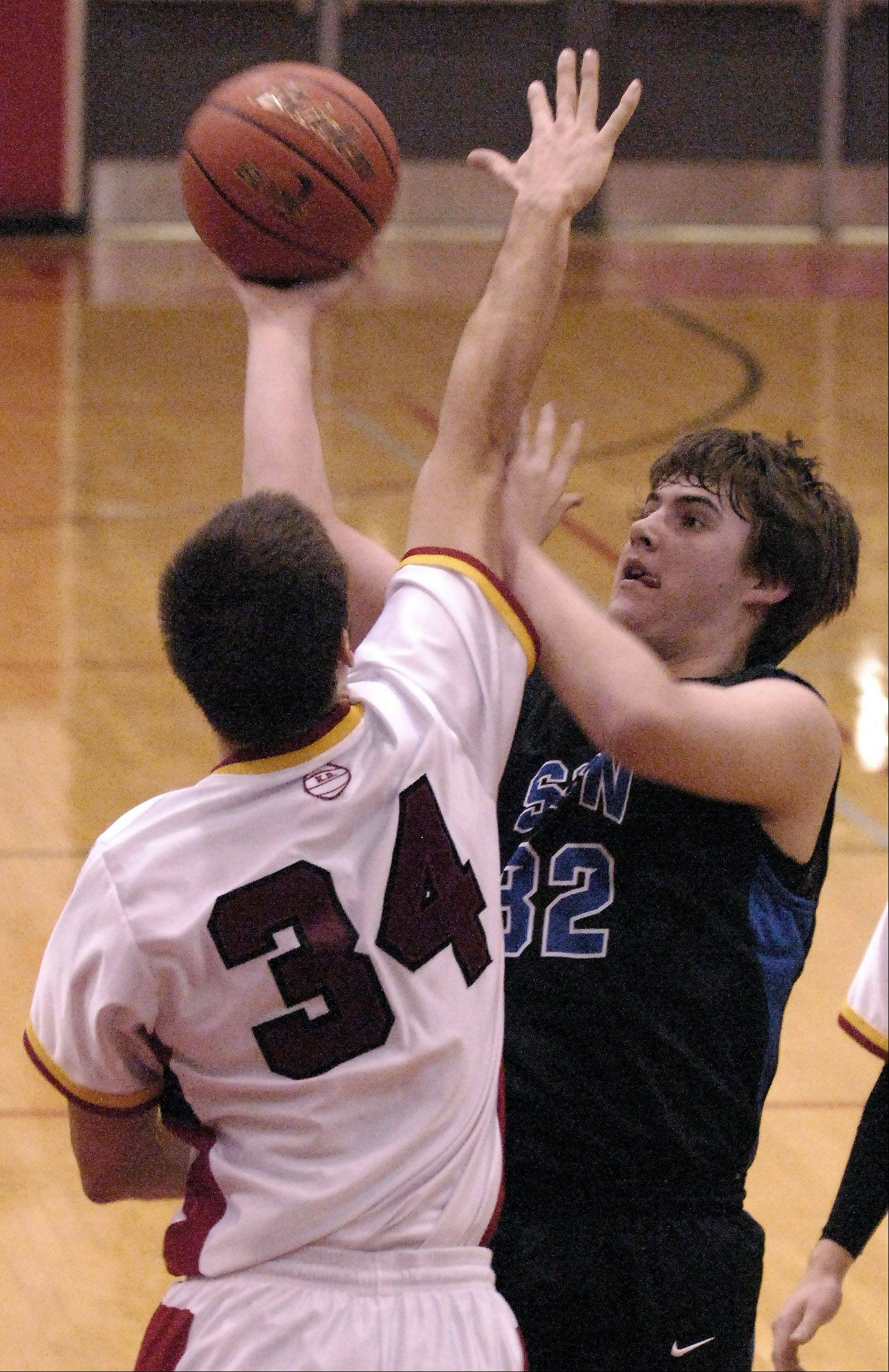 St. Charles North's Jack Callaghan puts up a shot against the defense of Batavia's Zach Strittmatter.