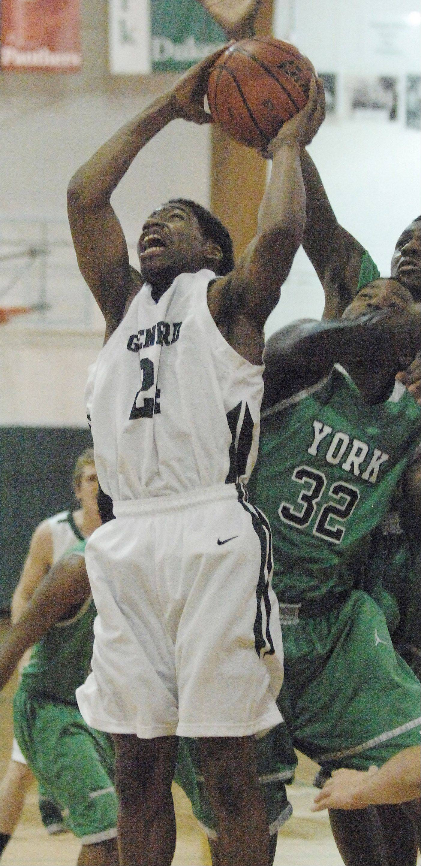 Keith Hayes of Glenbard West puts up a shot while Calvin Brown of York tries to knock the ball away during the York at Glenbard West boys basketball game Friday.