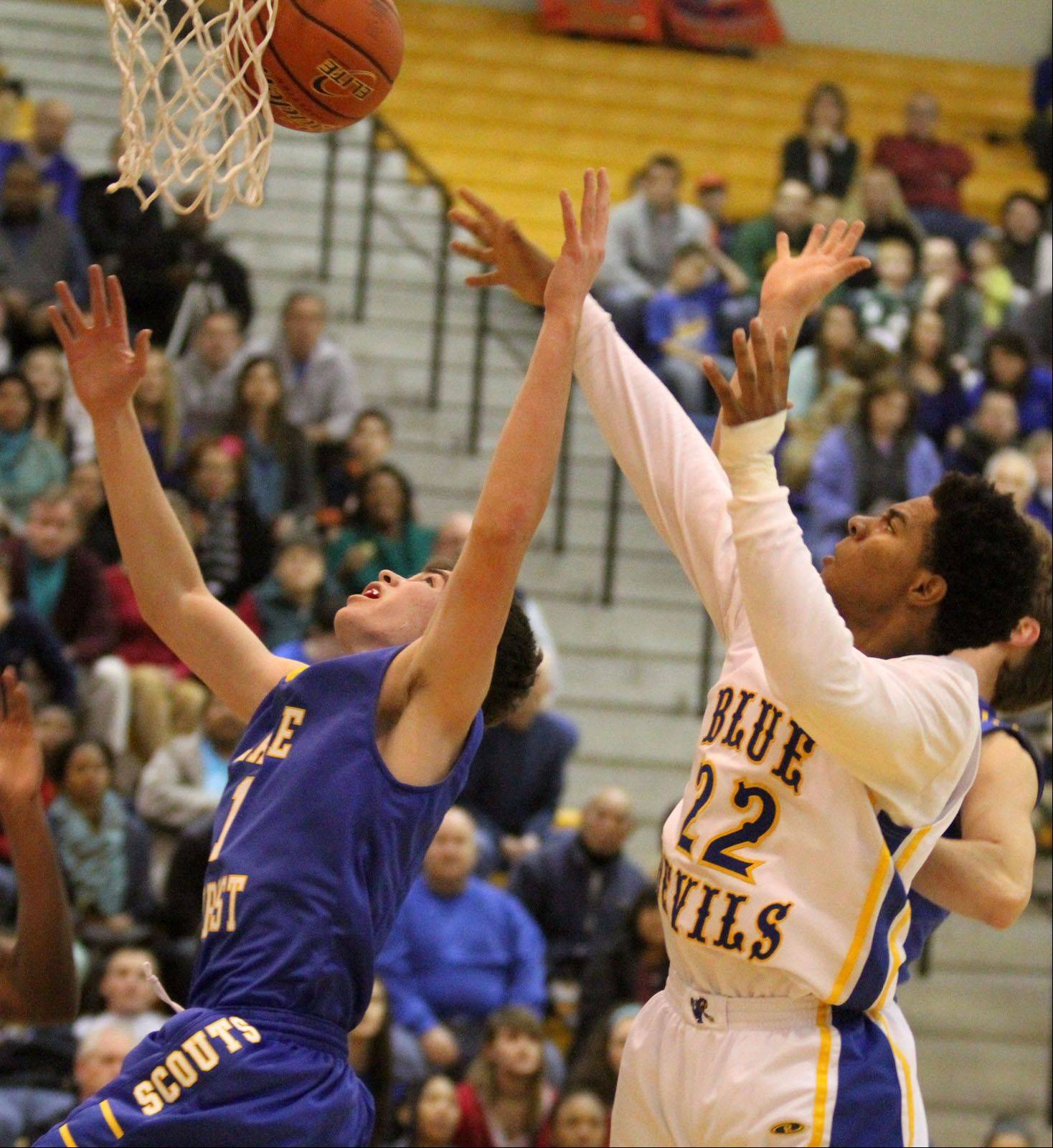 Warren's Dominic Cuevas leaps for a rebound against Lake Forest defender Ben Simpson.